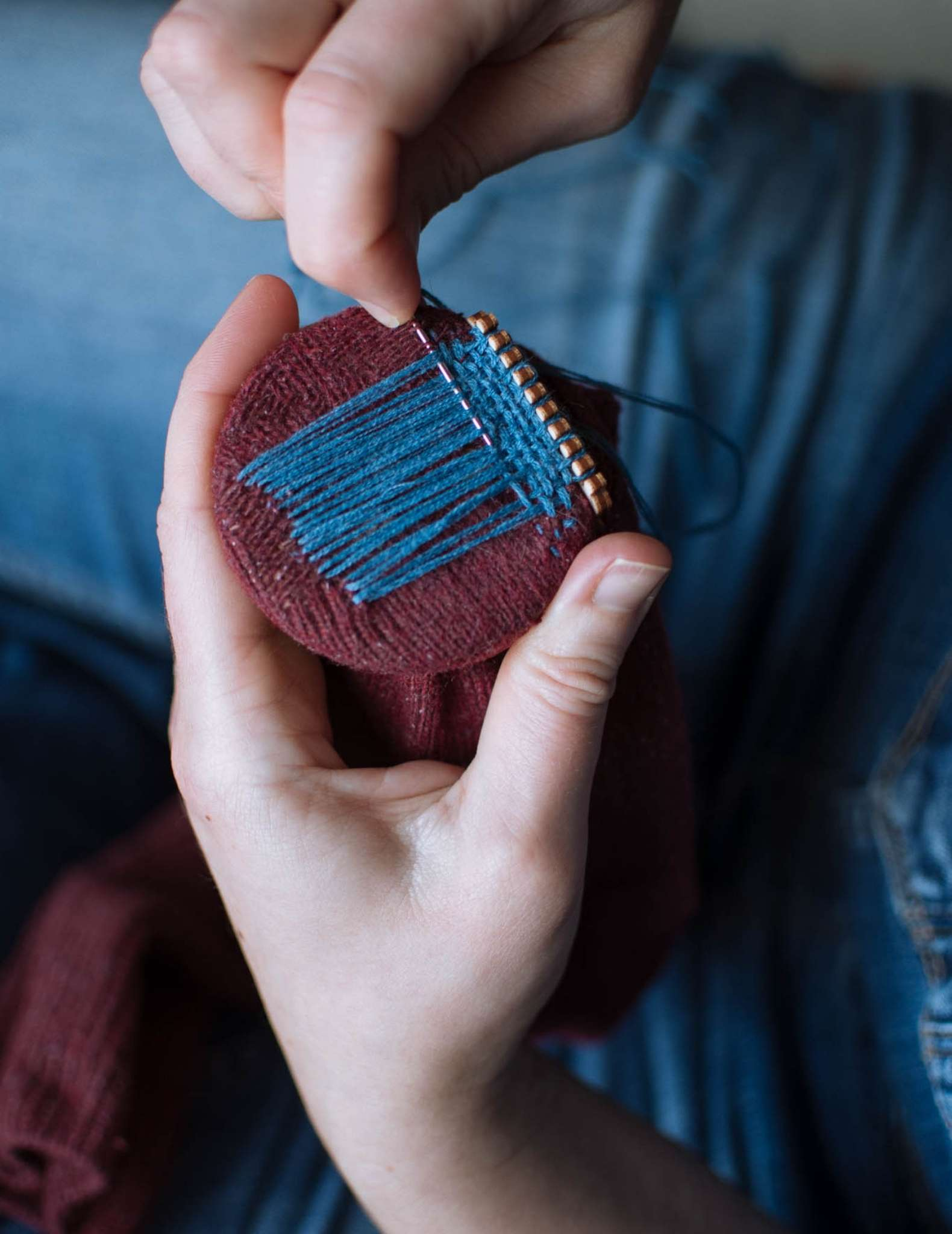 A model holds a burgundy sock while darning it with teal blue thread, using a wooden darning loom.