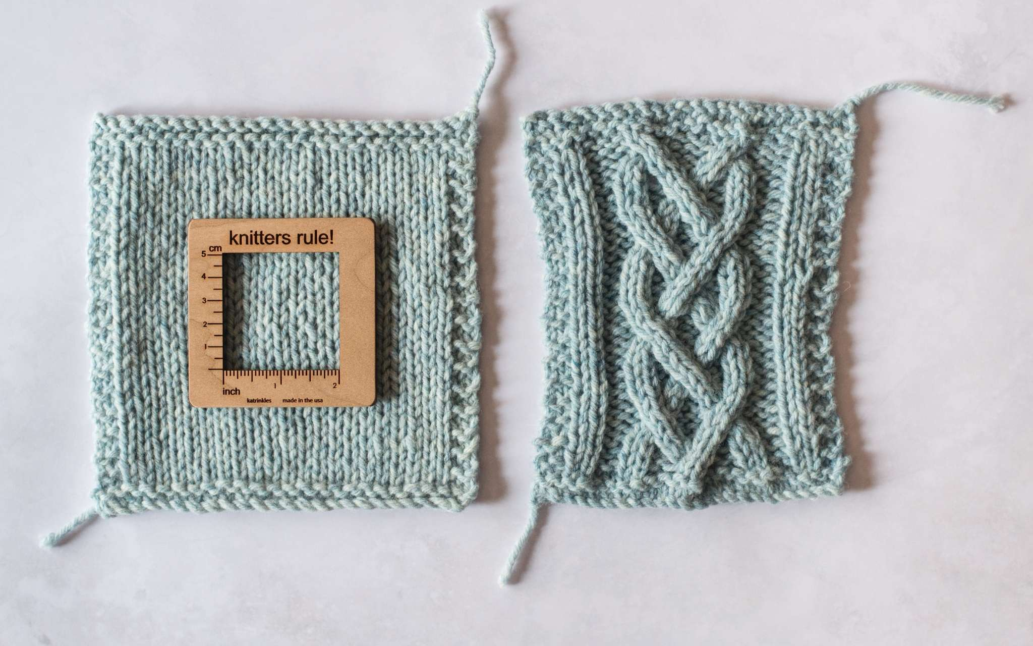 Two swatches lie next to each other. The left swatch has been knitted in stocking stitch and has a wooden measuring tool on top. The swatch in the right is in the same yarn but has been knitted in a more dense cabled pattern.