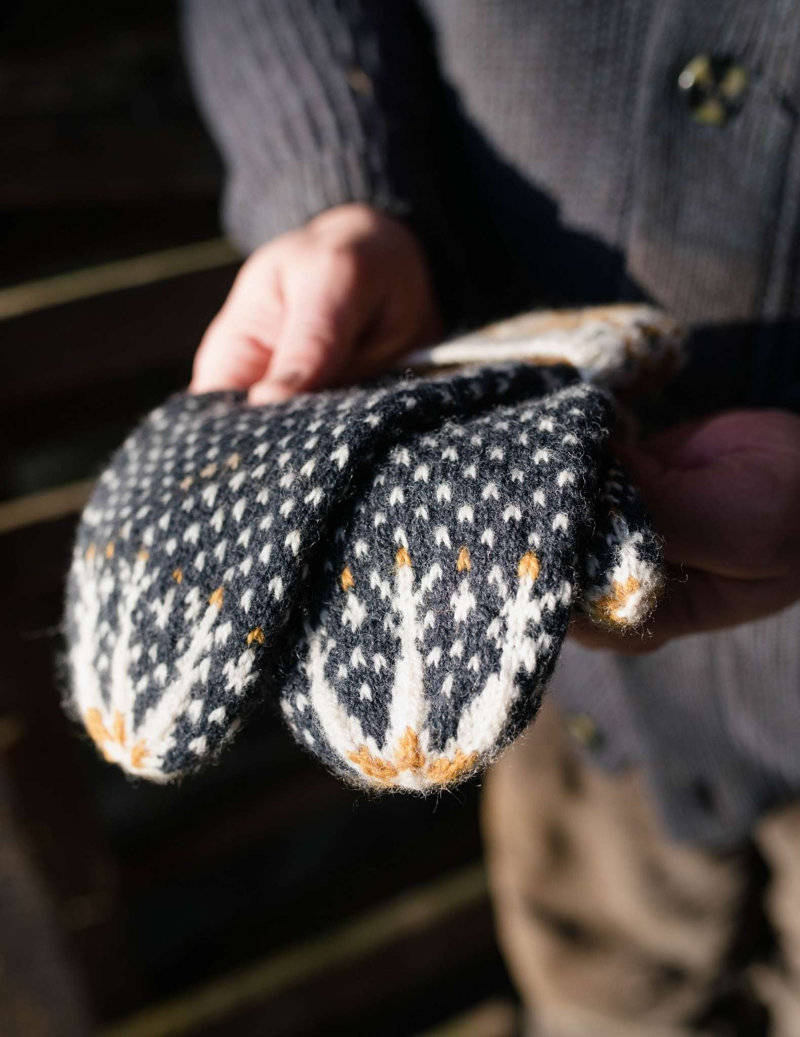 A pair of colourwork mittens in dark blue, white and yellow are held flat, unworn by a pair of white hands outdoors.