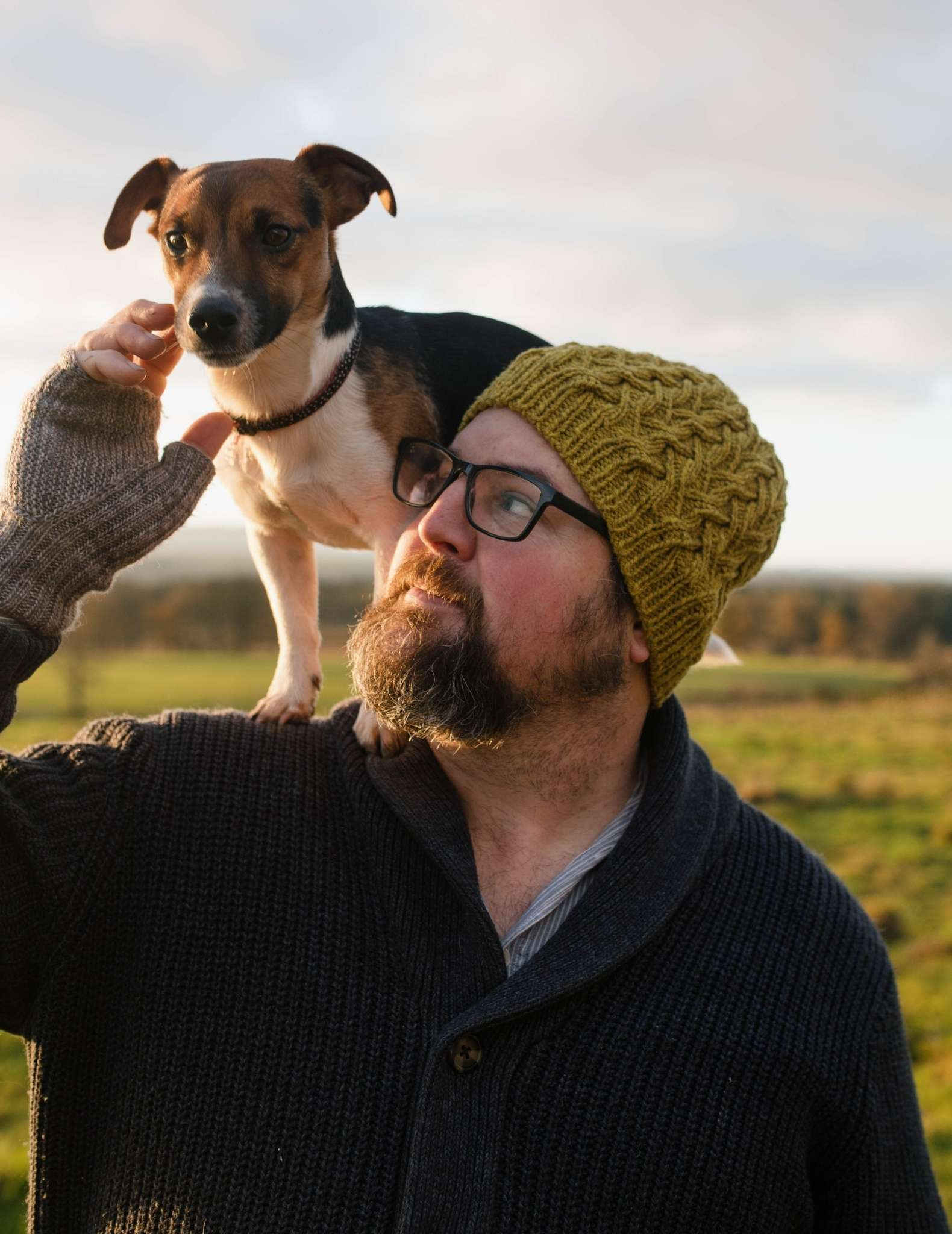 A white man with a beard and glasses stands in a field wearing a cabled green beanie hat. There is a small brown, white and dark dog standing across his shoulders and he has his hand raised towards it.
