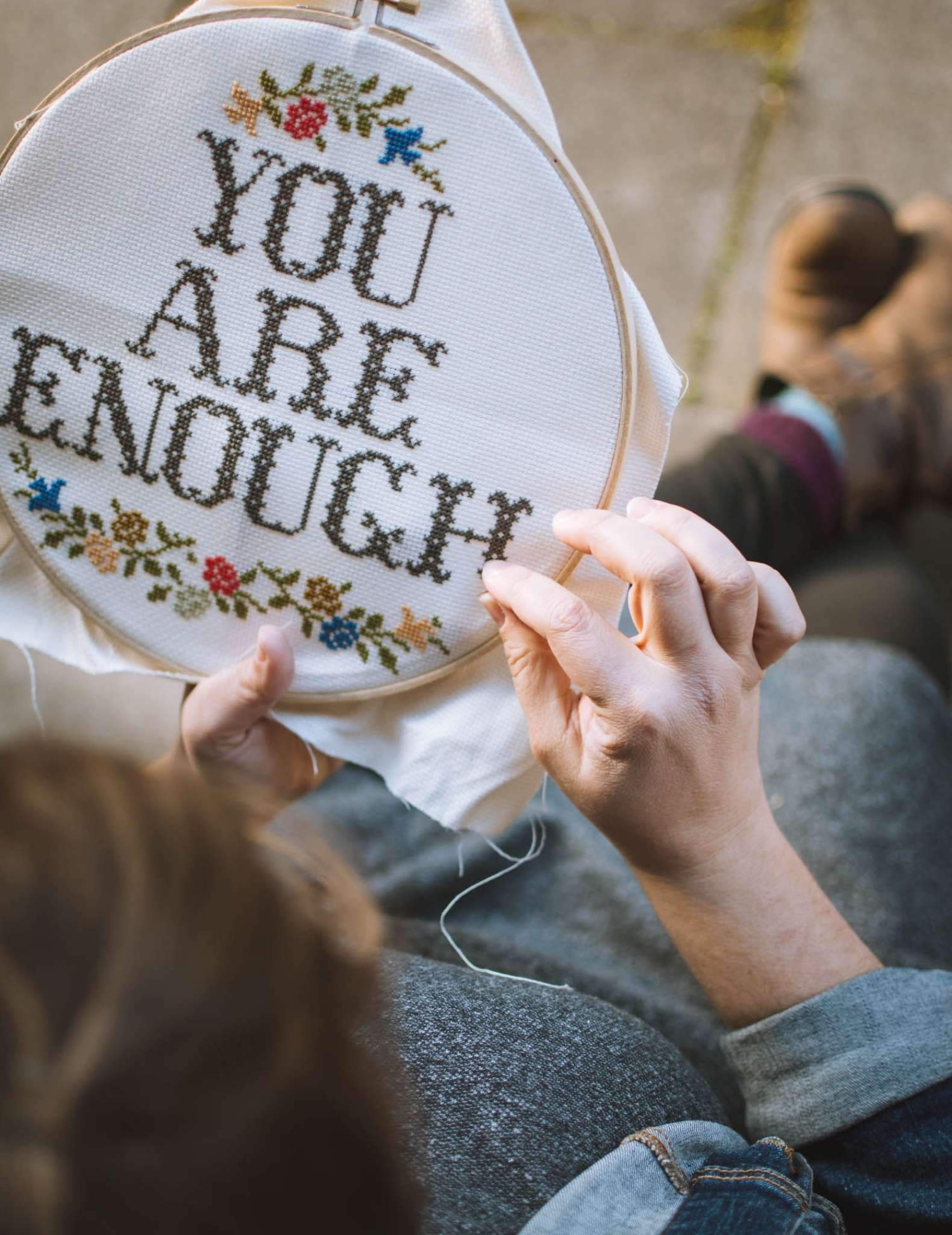 A white model with brown hair embroiders a cross stitch piece in a hoop showing the text 'You are Enough'