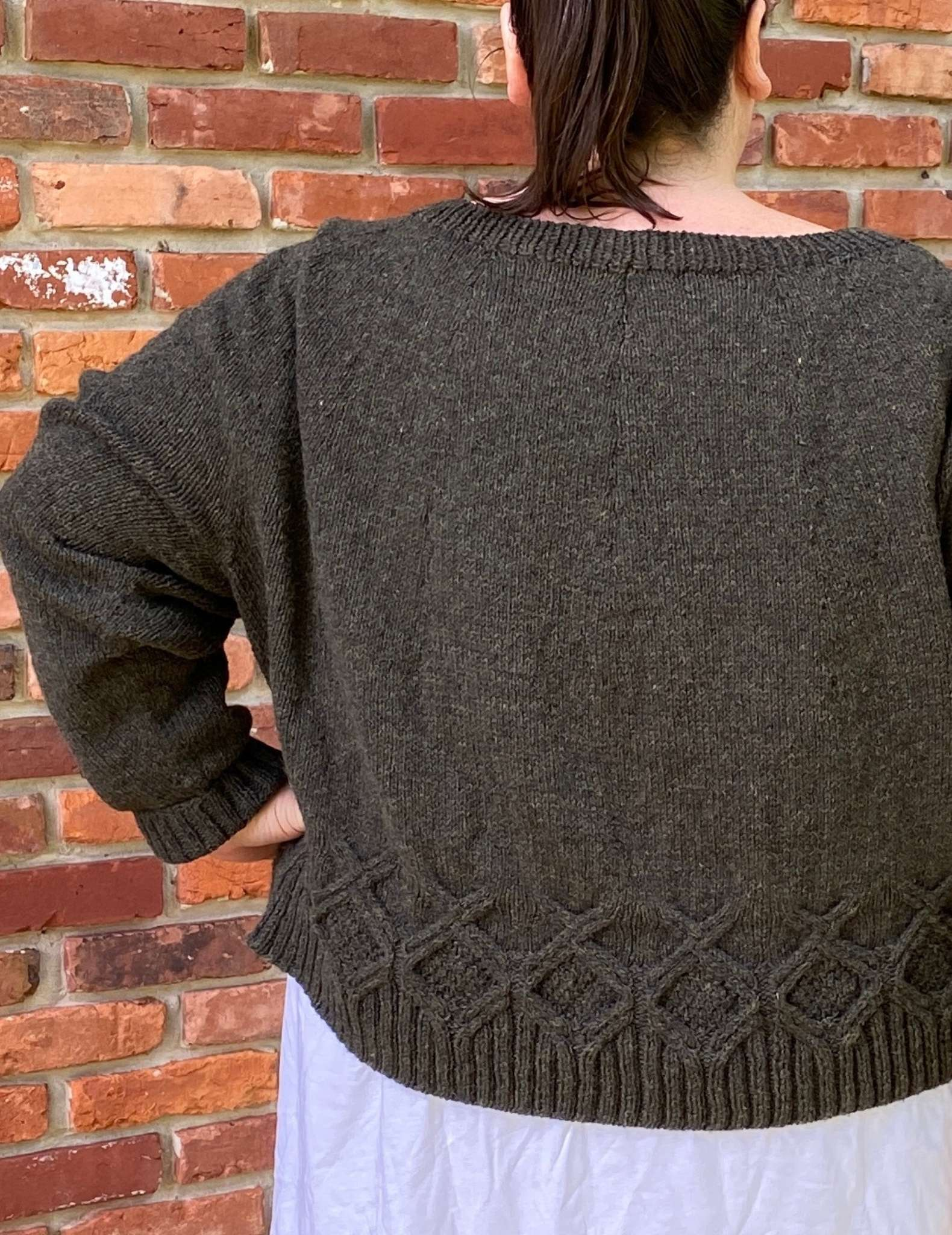the back of a brown sweater, worn by a model standing in front of a brick wall