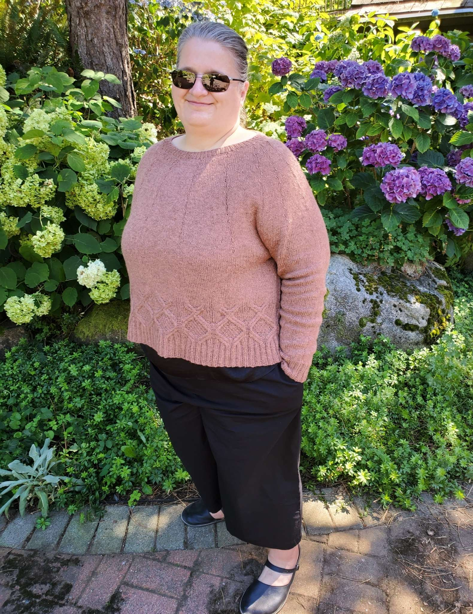 a model in a pale cropped cabled sweater standing in a garden next to flowers