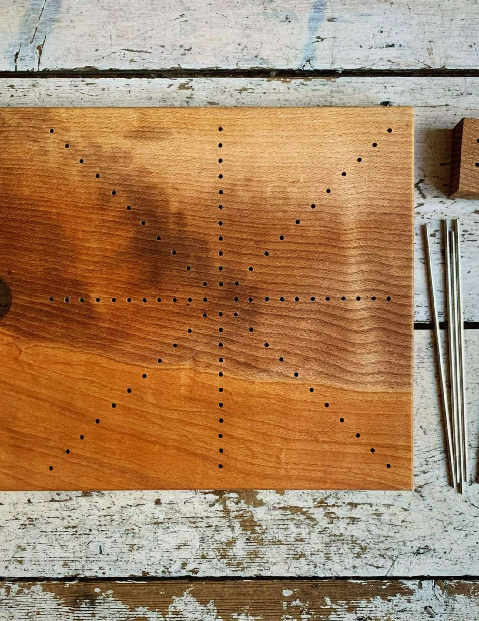 A wooden board marked with holes in diagonal lines over the surface, with blocking pins laying at the right side.