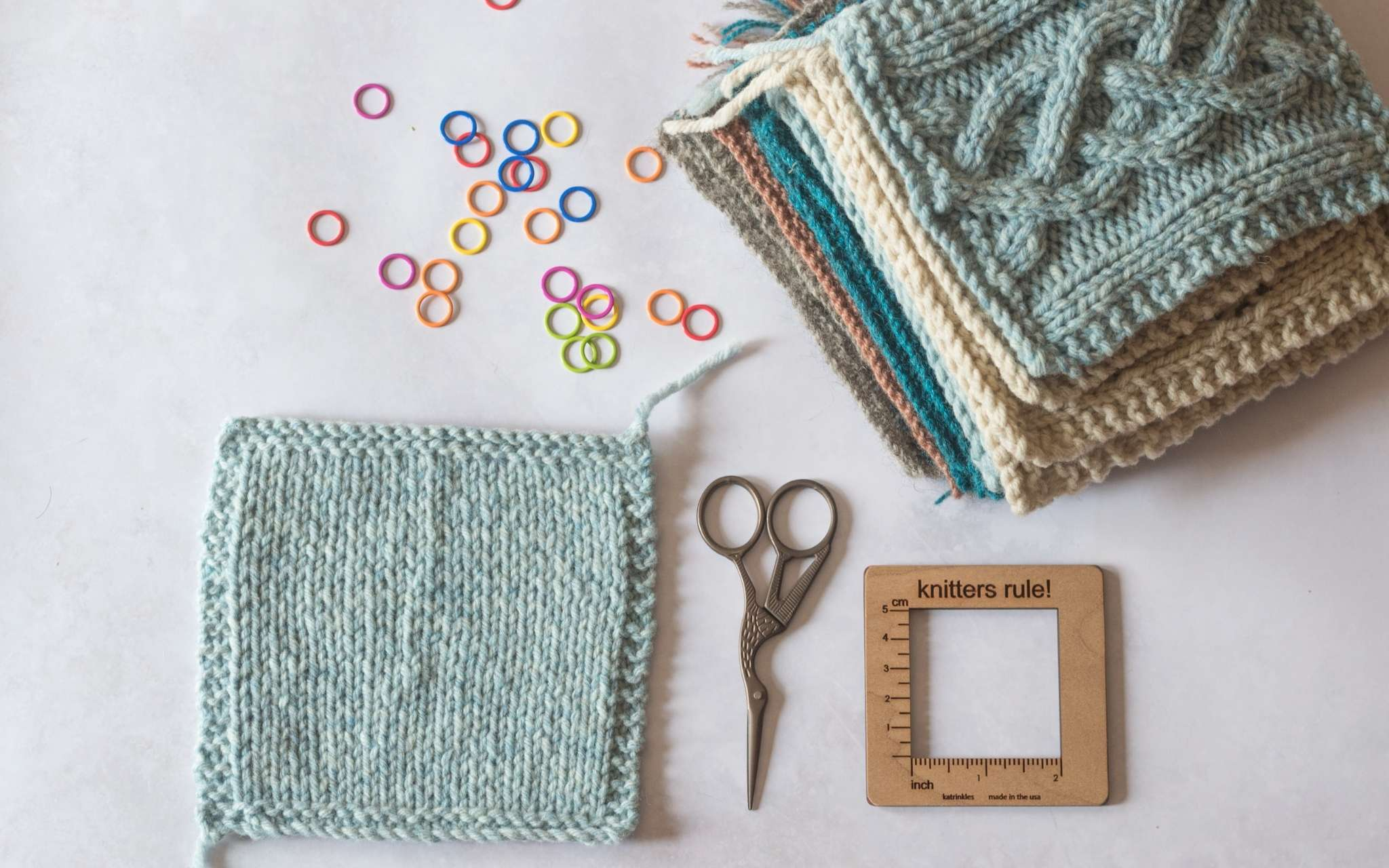 A blue stocking stitch swatch lies on a pale flat surface. Next to it is a small pair of scissors, a wooden gauge tool, coloured stitch markers and a pile of swatches.