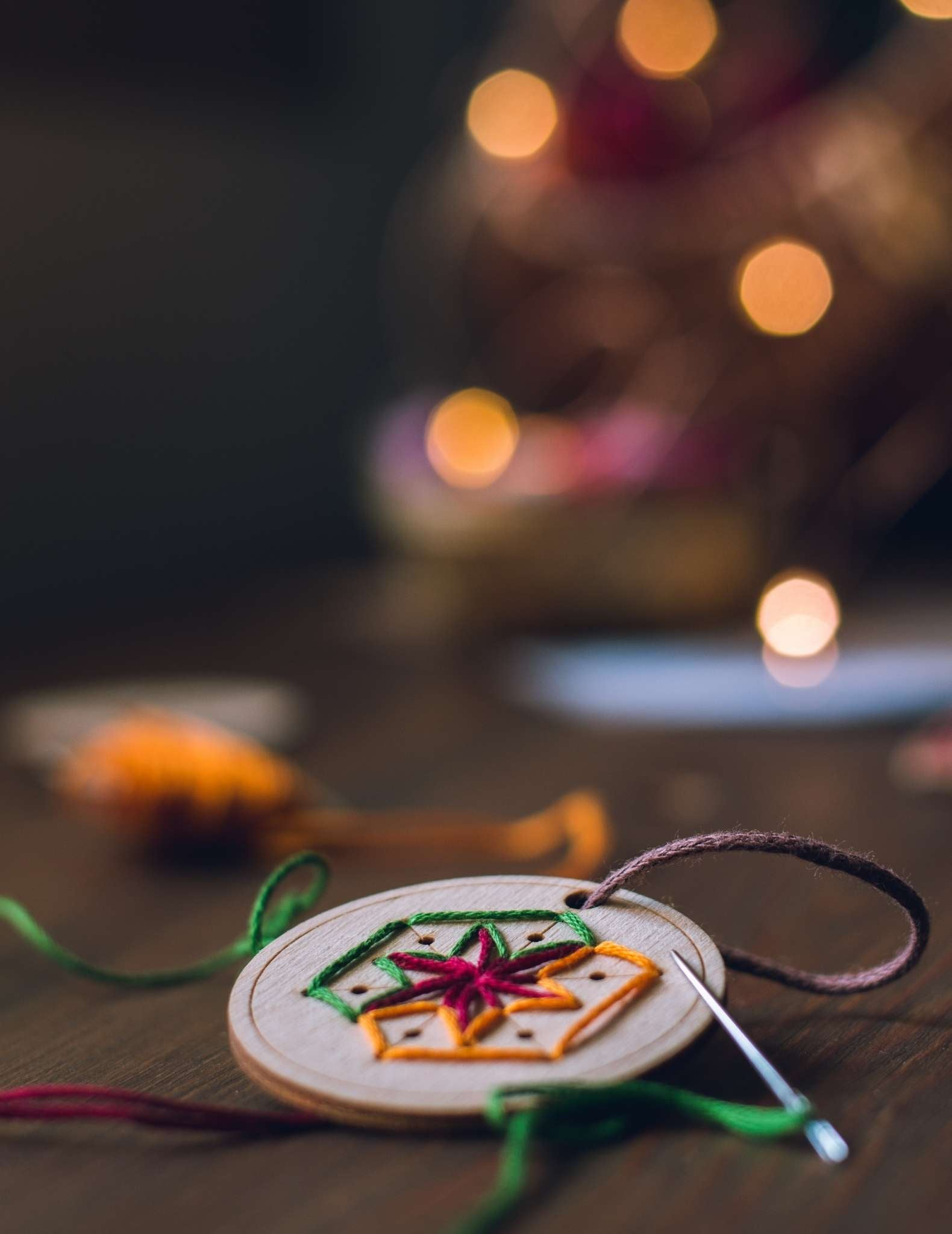 A circular wooden ornament is being hand stitched in a snowflake motif with brightly coloured threads. It lies on a table in front of a tree with fairy lights.