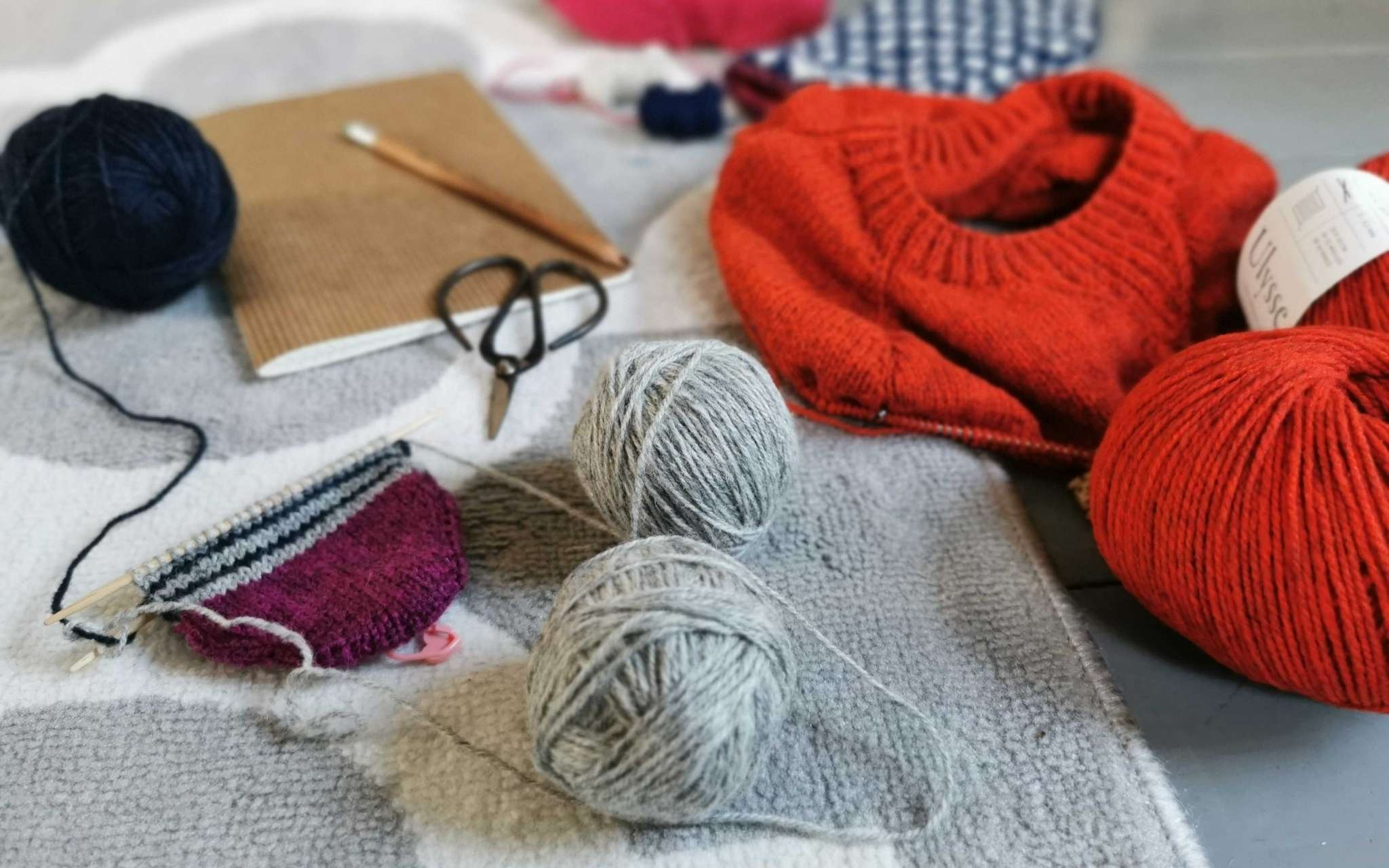 A pile of knitting projects on the needles including an orange sweater, striped socks next to a notebook and pencil.