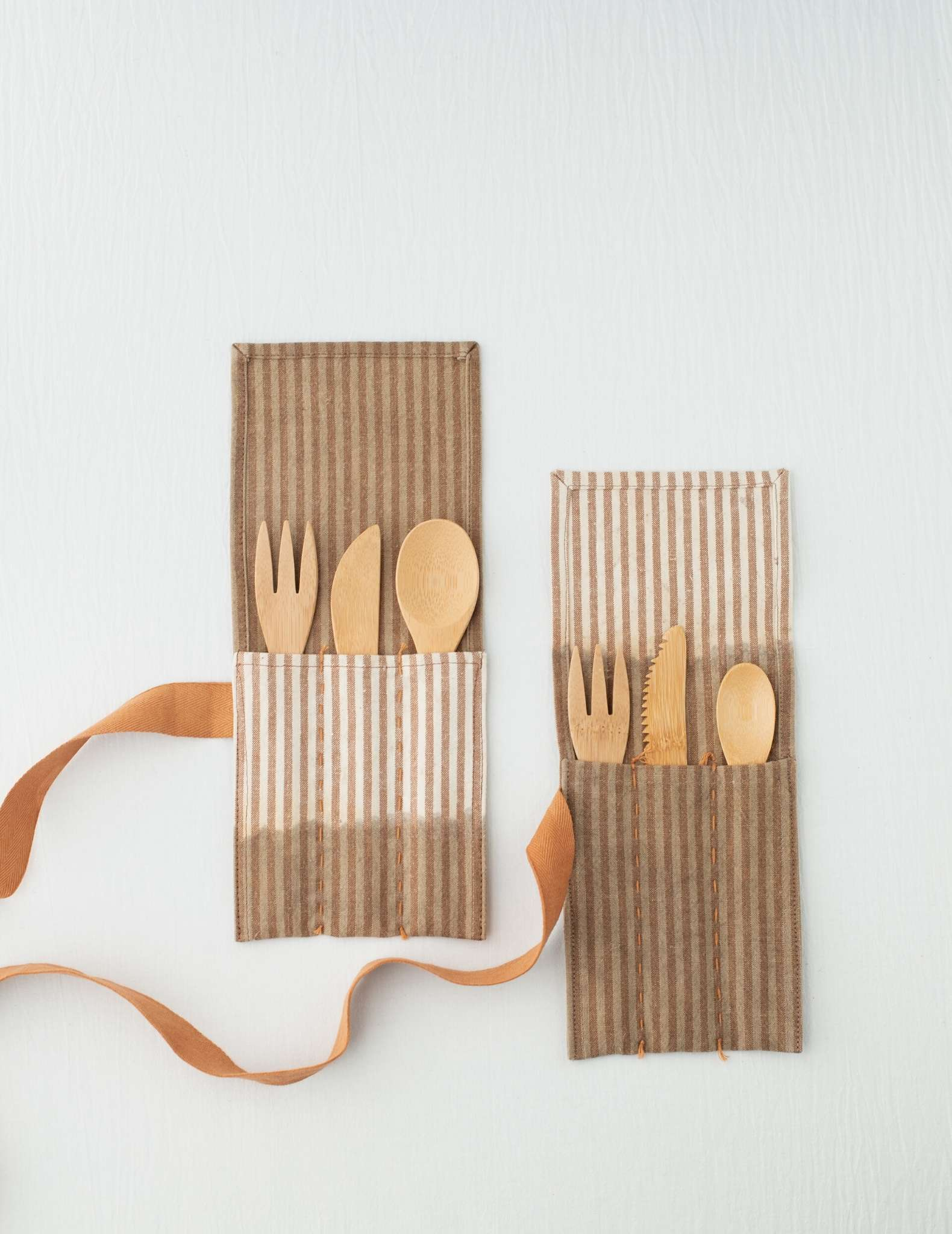 Two brown and natural patterned utensil rolls laying flat on a white surface with ribbon closures hanging to the side. They are filled with a wooden fork, knife and spoon each.