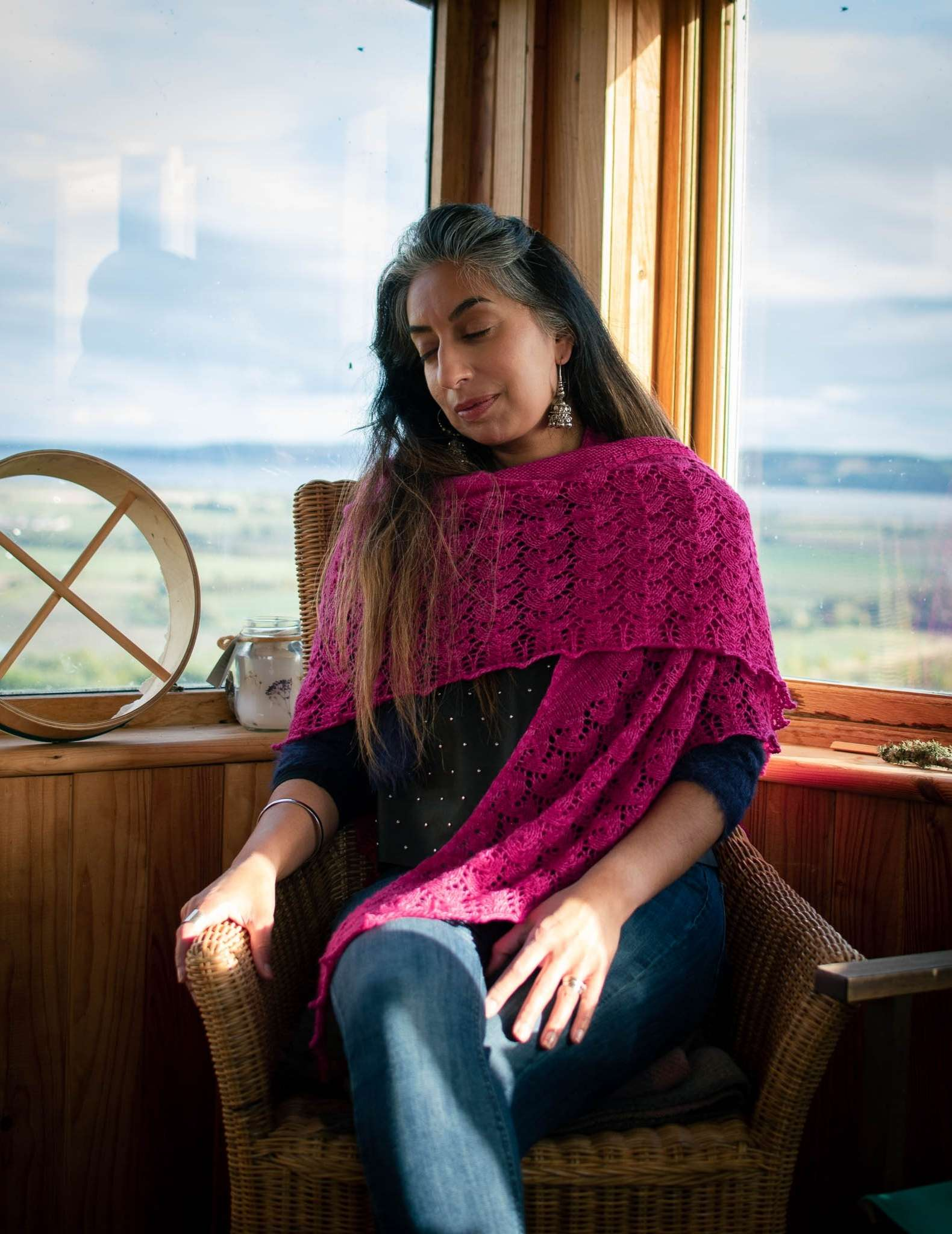 A woman with dark hair sits in front of a window showing a rural landscape. She is wearing a bright pink lace shawl and jeans, is looking down and has her legs crossed. She sits on a wooden chair.