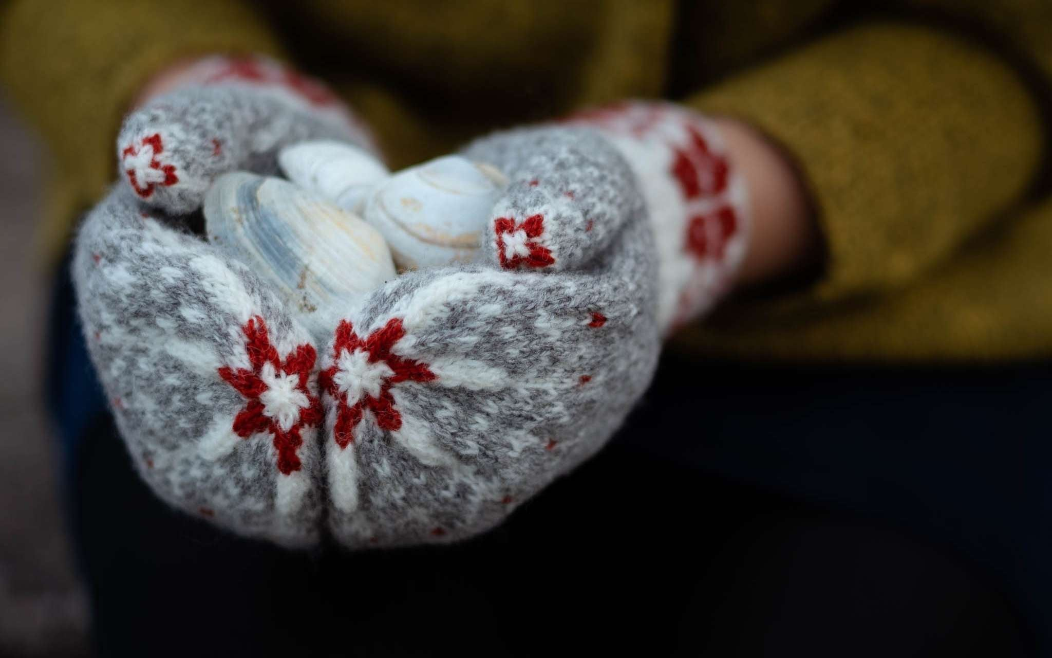 Two hands wearing grey, white and red colourwork mittens are clasped together holding a pale grey stone.