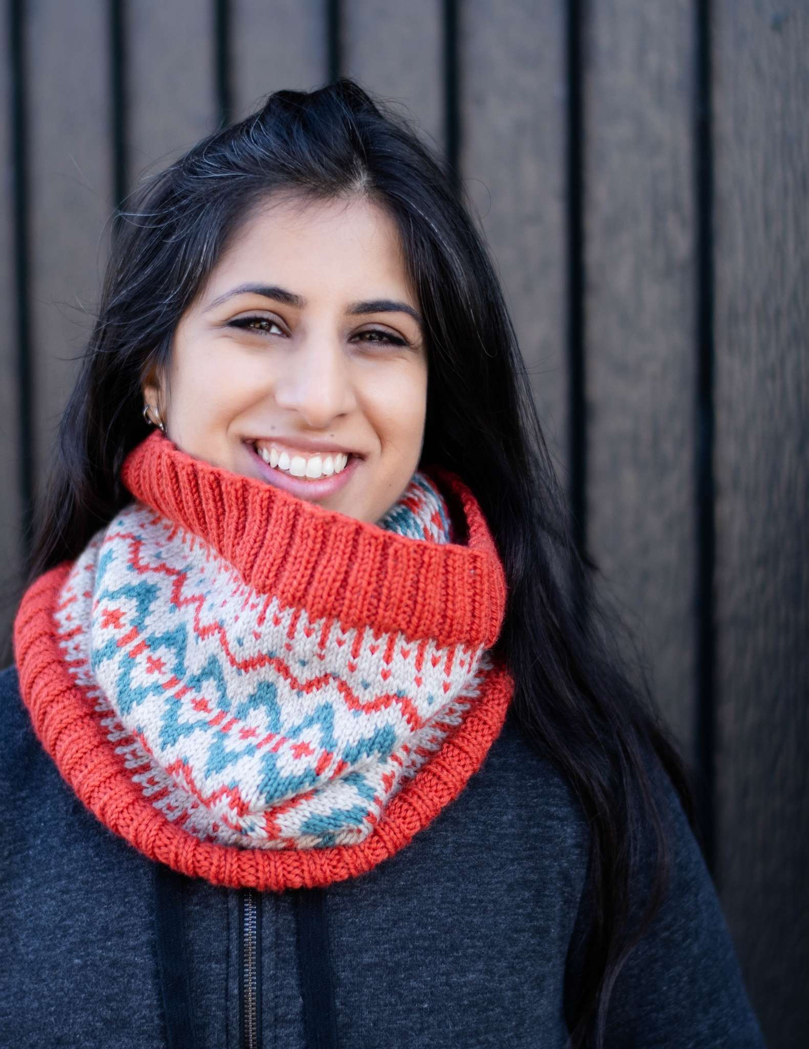 a woman with dark hair wears a red, white and teal colourwork cowl, she is smiling