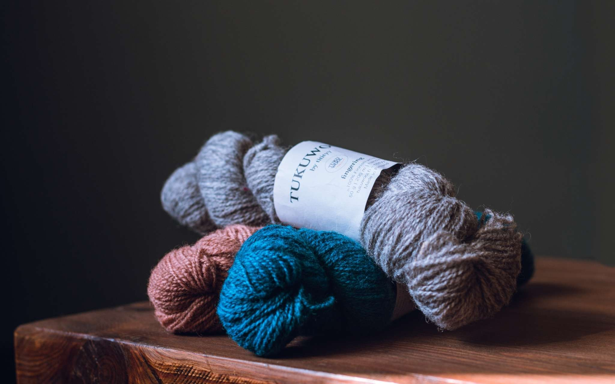 Three skeins of yarn in grey, blue and coral lie piled on top of each other on a table.