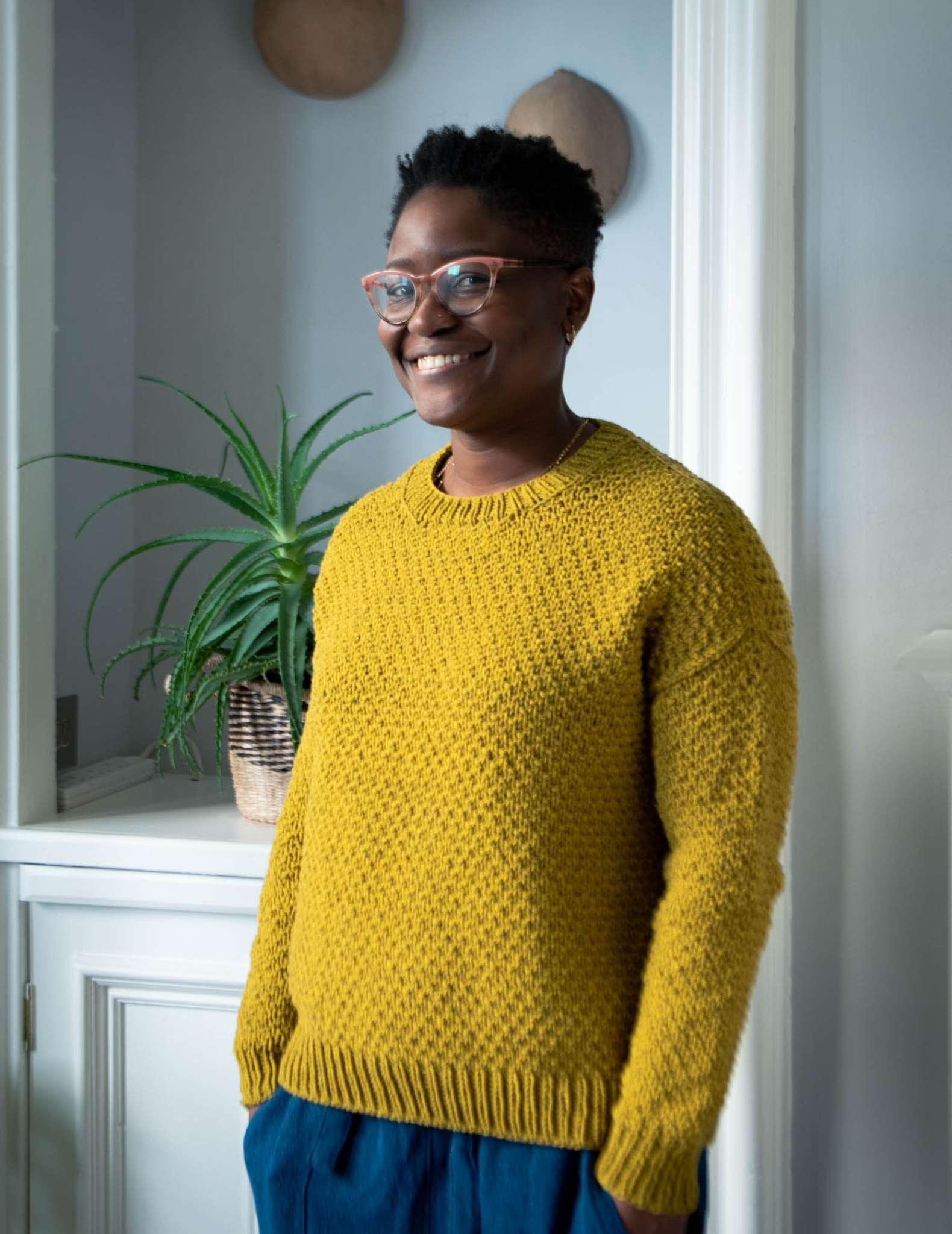 a black woman stands indoors with a houseplant behind, wearing a gold textured sweater with hands in her pockets