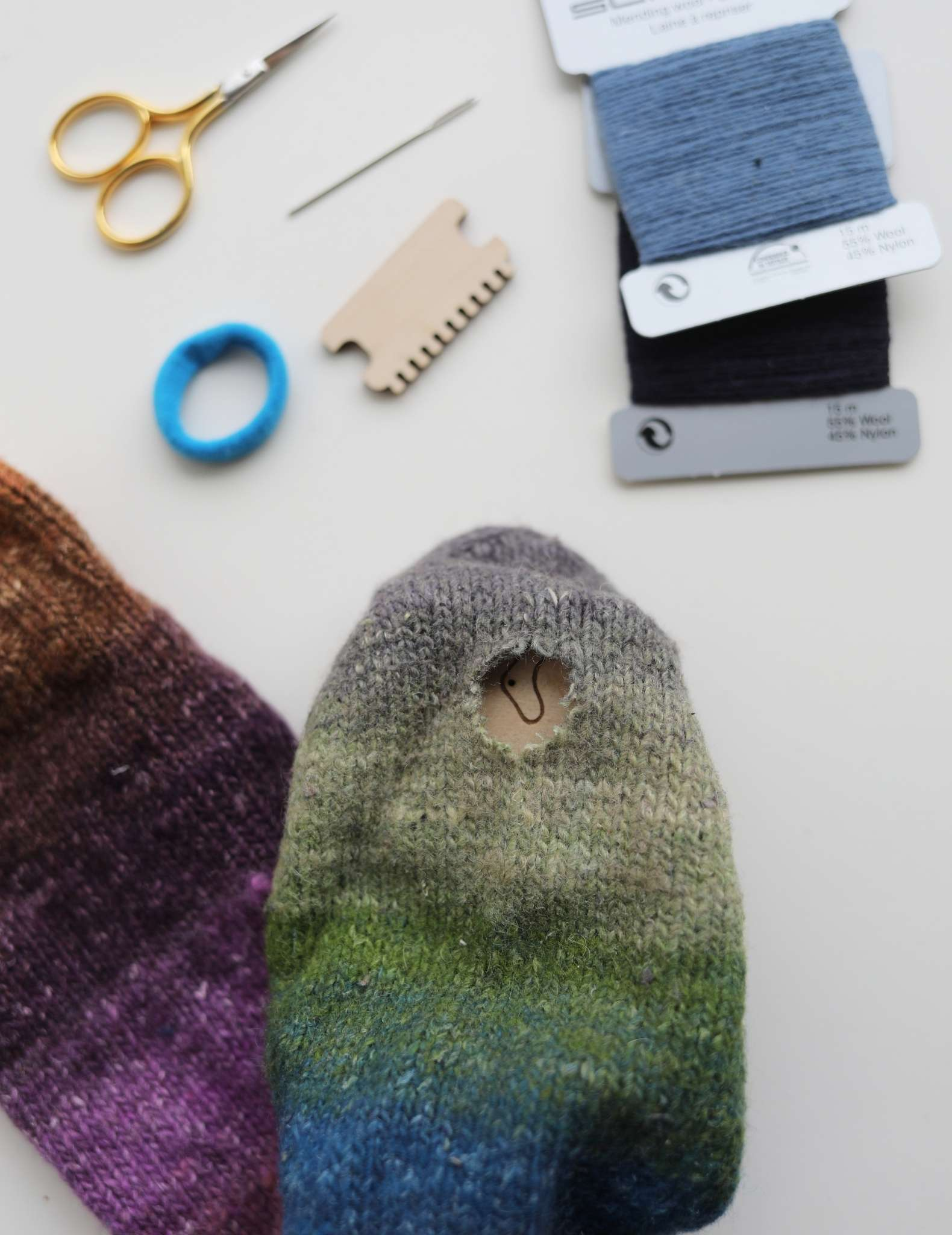 A multicoloured sock lies folded over, with a hole in the centre of the foot, near the toe. Above the sock is small yellow scissors, a needle, a darning loom and blue and black mending thread.