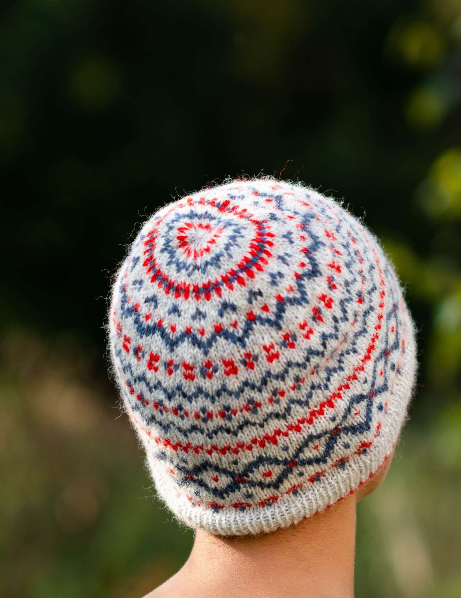 a model wears a colourwork beanie hat in cream, red and blue and faces away from the camera