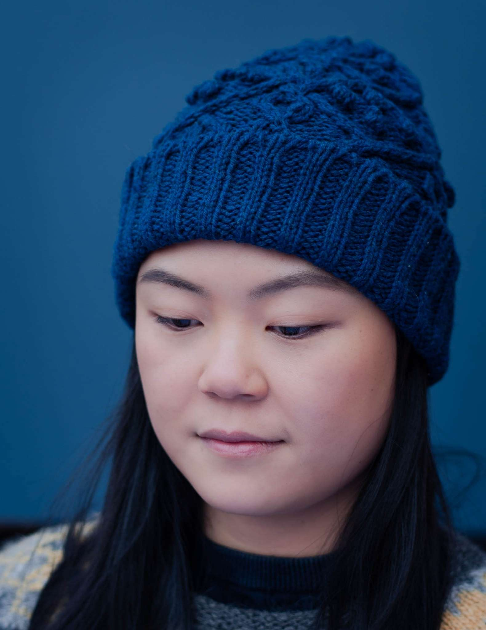 a close up of a young woman with straight dark hair looking down, she is wearing a cabled blue hat against a blue background