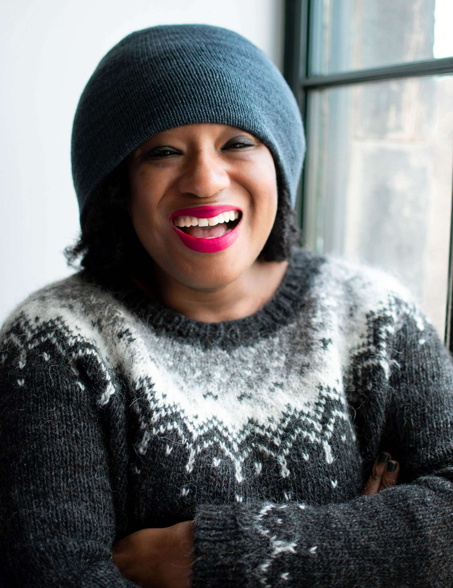 A close up of a black woman with bright pink lipstick wearing a teal beanie hat and colourwork sweater in blacks and neutral colours.