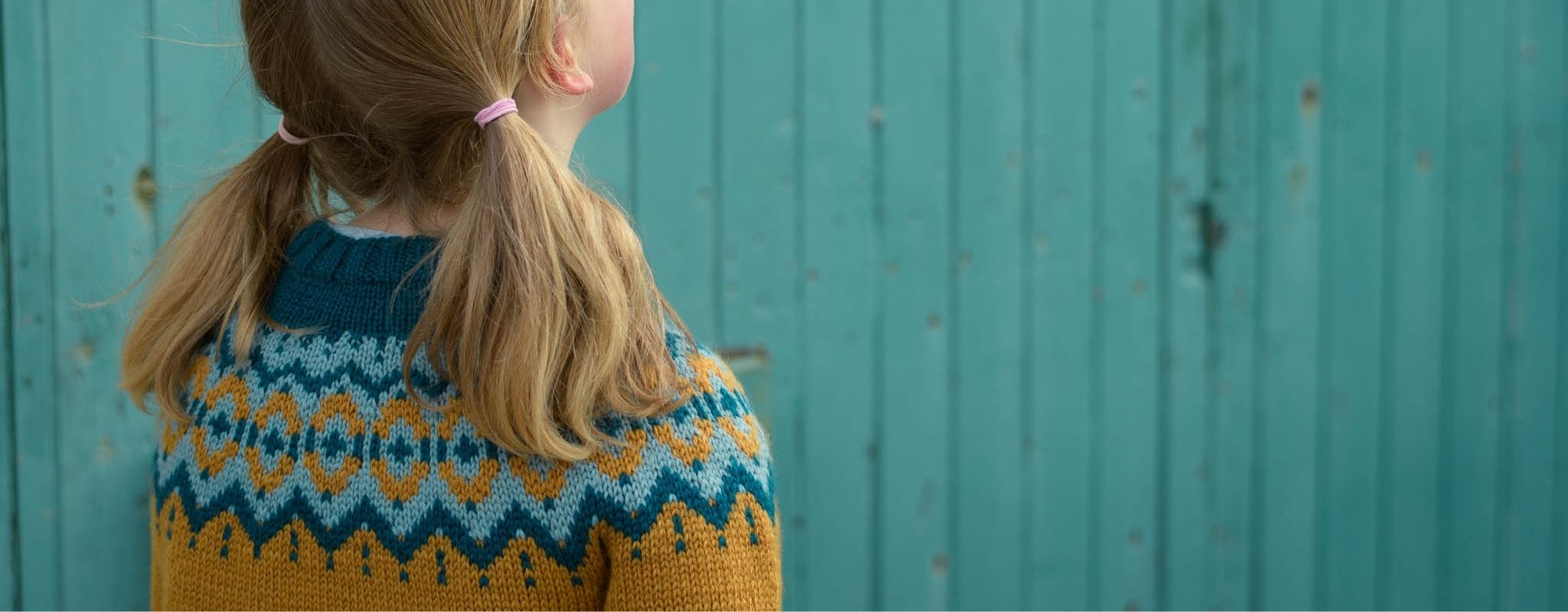 Cropped image showing a blond child with pigtails looking away from the camera, wearing the Brunstane Sweater in the vintage palette. The background is a turquoise painted wooden wall.