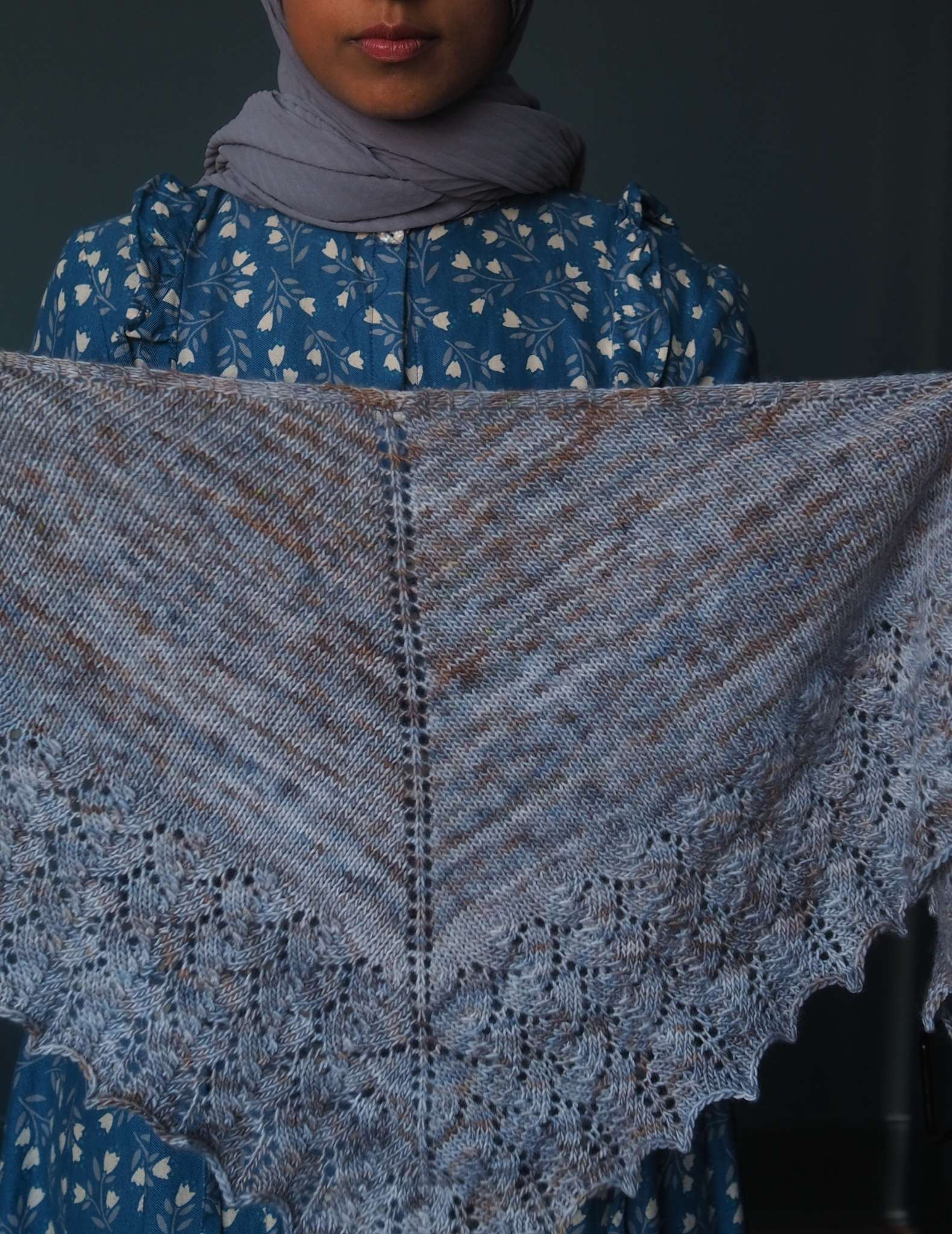 A brown woman in a hijab wearing a floral blue dress holds a blue and grey triangular shawl in front of her.