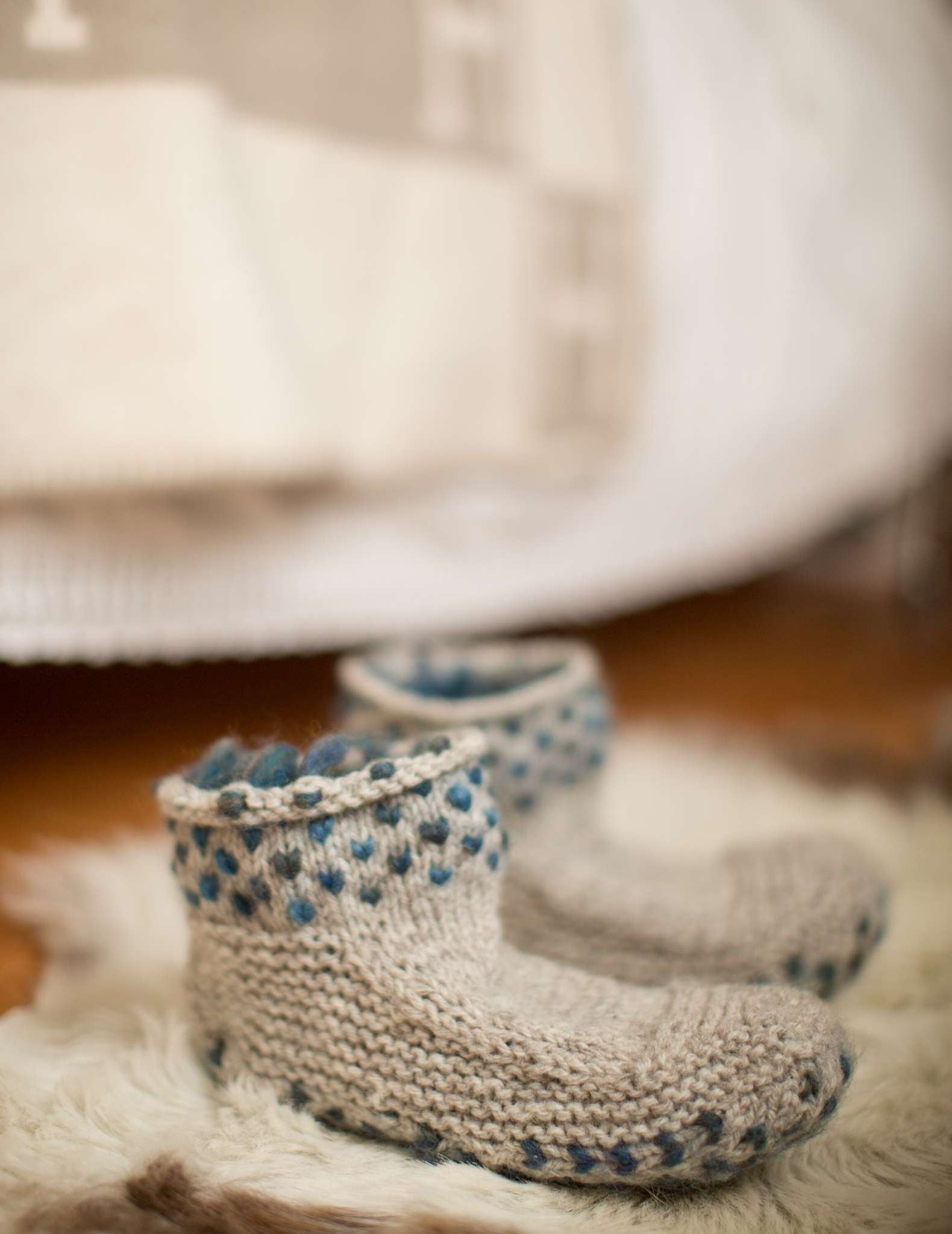 a pair of pale knitted slippers with a teal dot pattern around the cuff sit next to each other on a cream rug