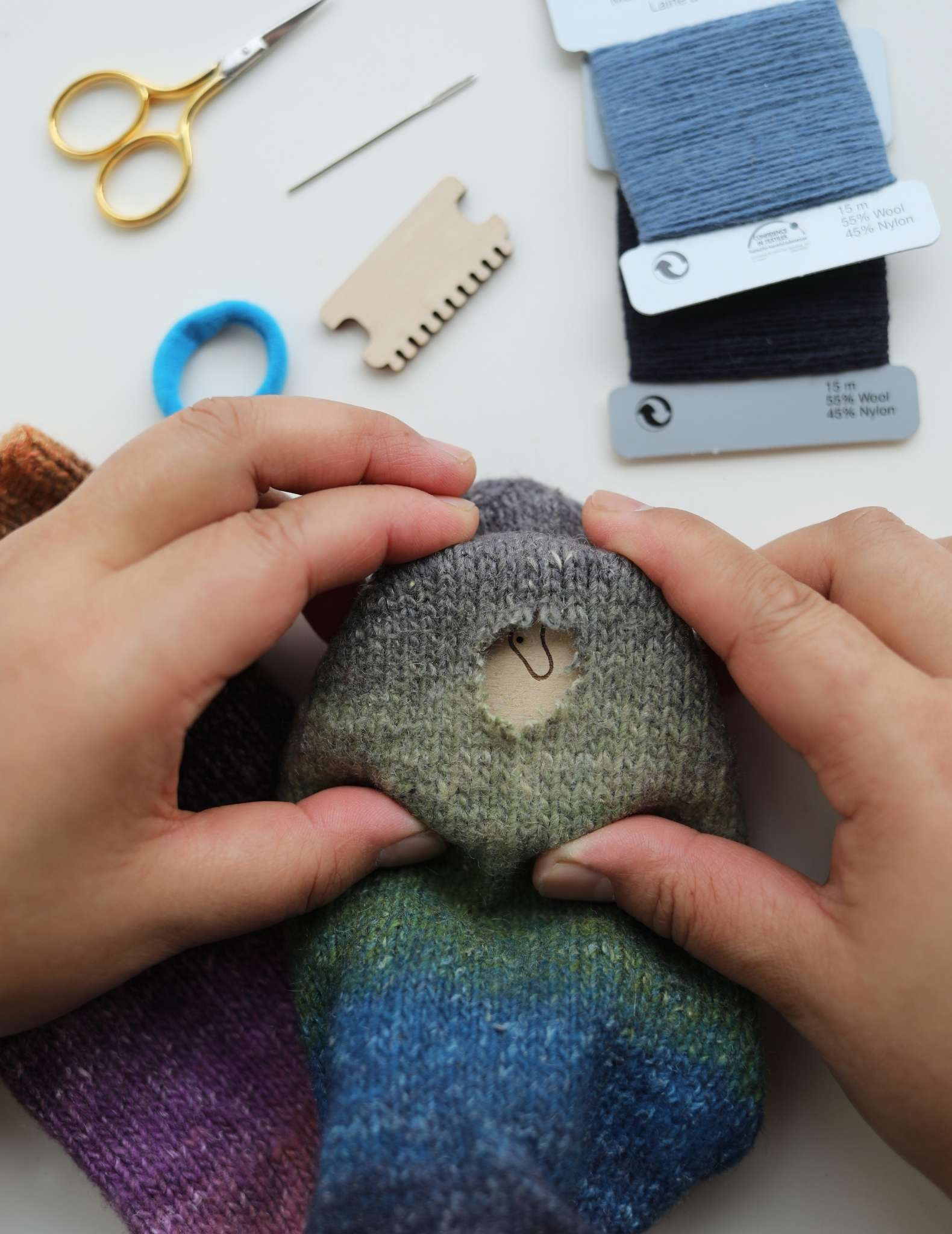 Hands hold a striped sock, with the hole showing between them. Inside the sock and underneath the hole is a wooden darning loom, with the wood visible through the hole.
