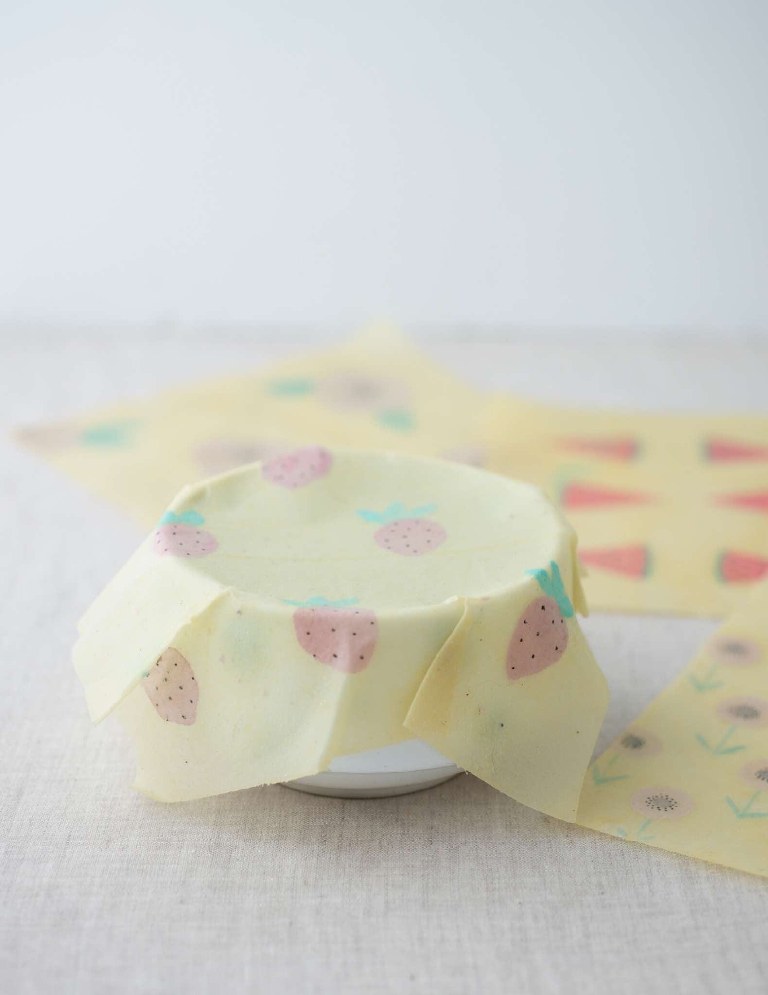 a white bowl covered in a pale food wrap that clings to the top edge of the bowl. The food wrap is handprinted with a strawberry motif and other, unused wraps lay behind.