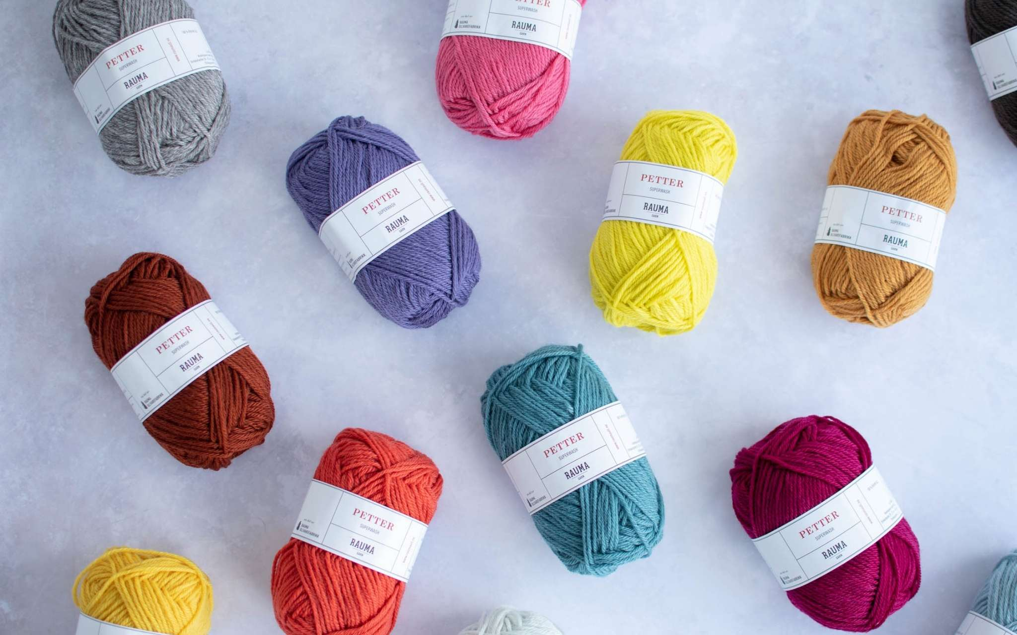 balls of brightly coloured yarn lie scrattered on a pale grey surface
