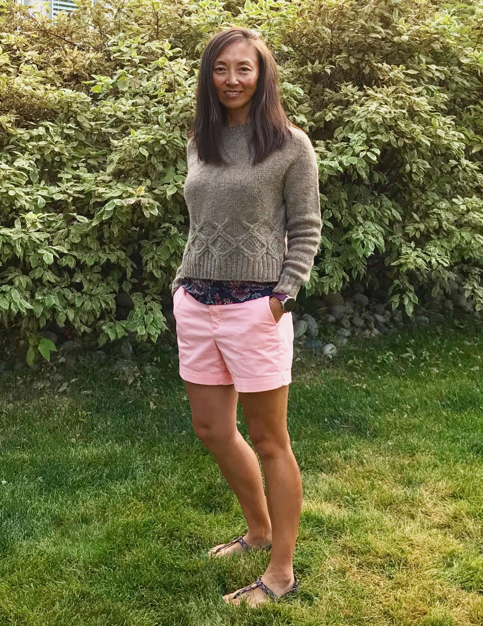 asian model with olive skin standing on grass wears neutral coloured sweater and pink shorts