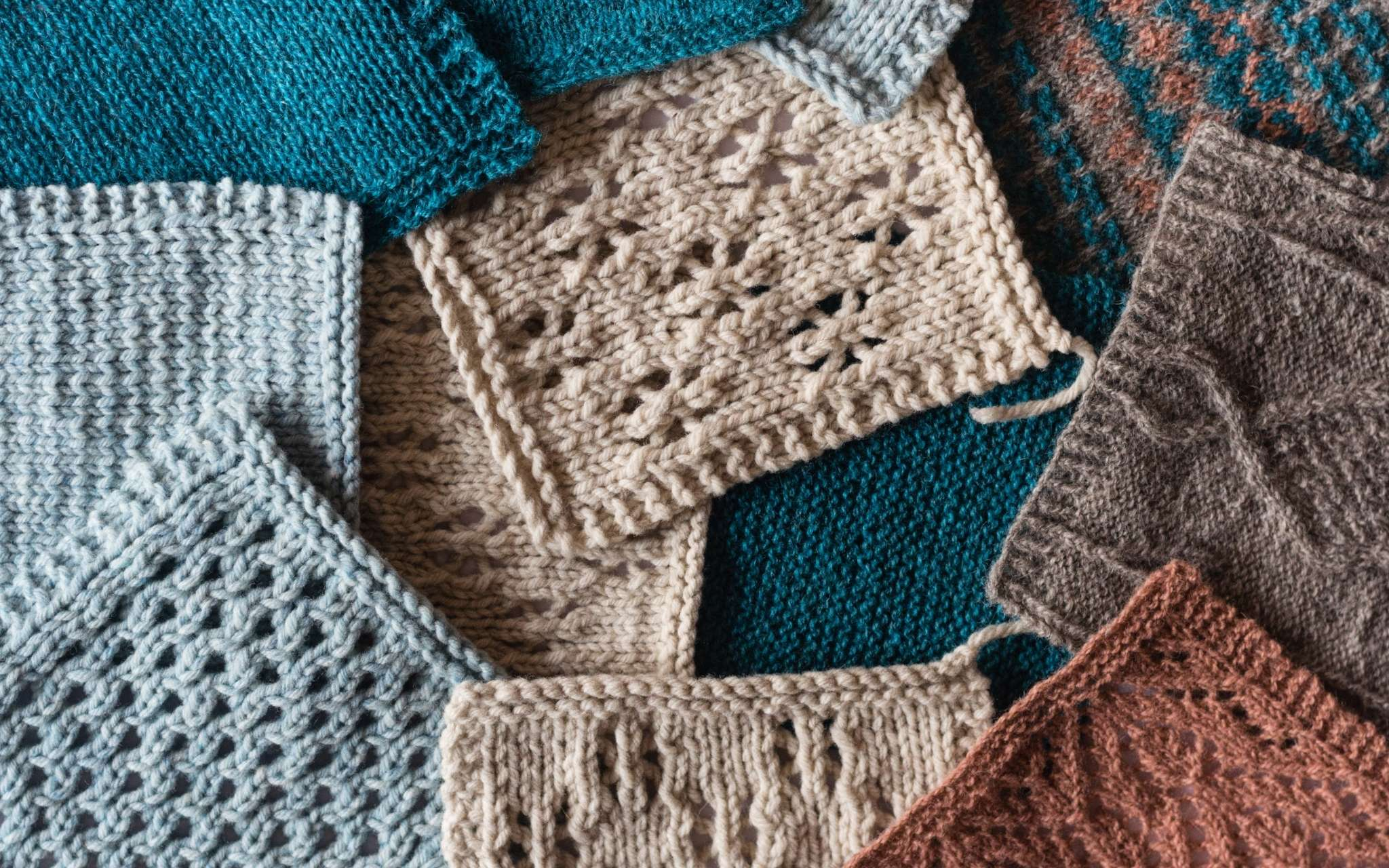 A pile of swatches, all laying flat and overlapping so that they are all that is visible. They are knitted in lace and textured stitch patterns in shades of beige, blues and brown.s