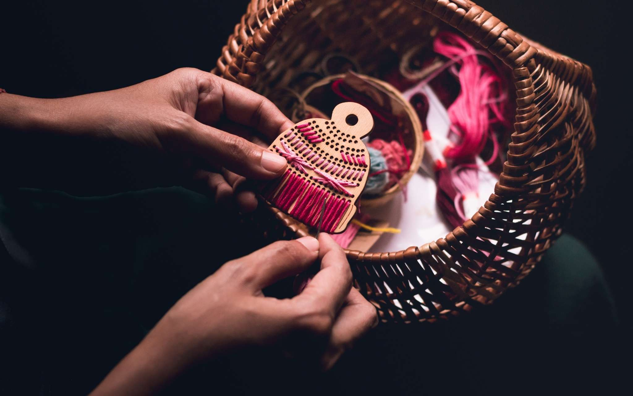 A hat shaped wooden tree ornament is held in hands as it's stitched with brightly coloured threads.