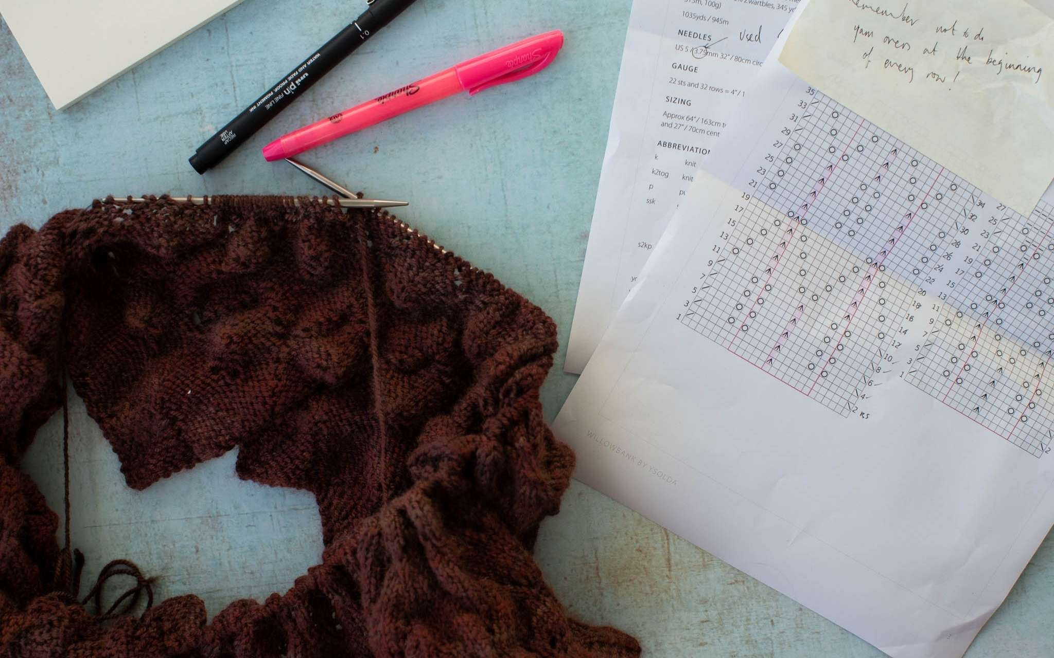 A brown lace knitting project lies on a blue surface next to a black and pink pen, the sheets of a paper knitting pattern and post it notes.