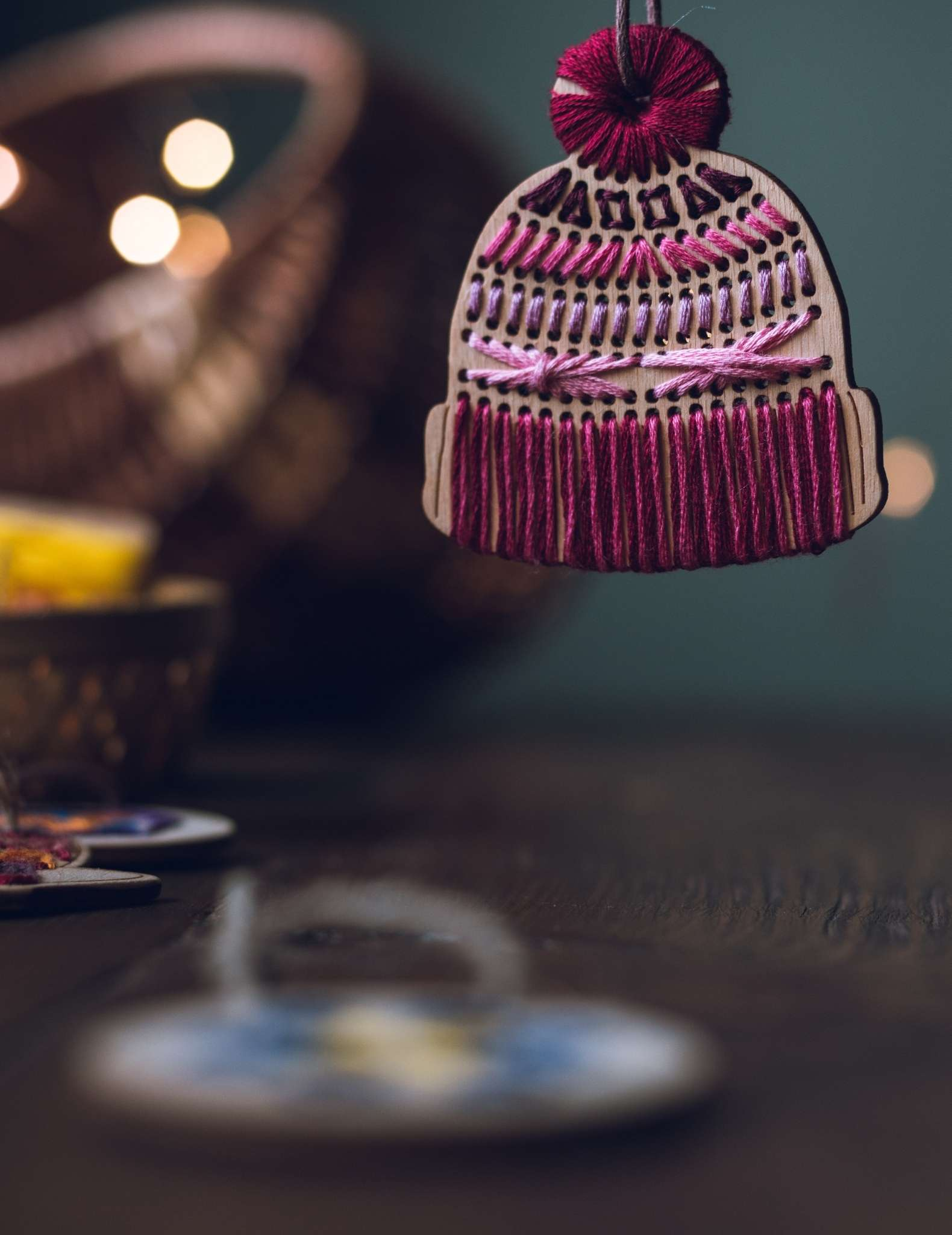 A close up of a wooden ornament shaped like a knitted hat with pom pom, stitched with pink threads.