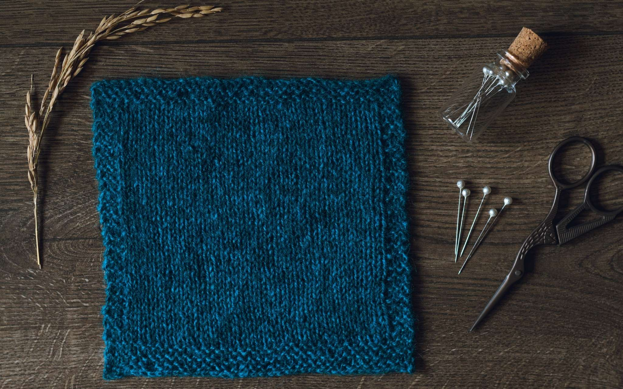 A swatch of stocking stitch in dark blue laid flat on a wooden surface. There are some dried stems, scissors and a bottle of pints to the side.