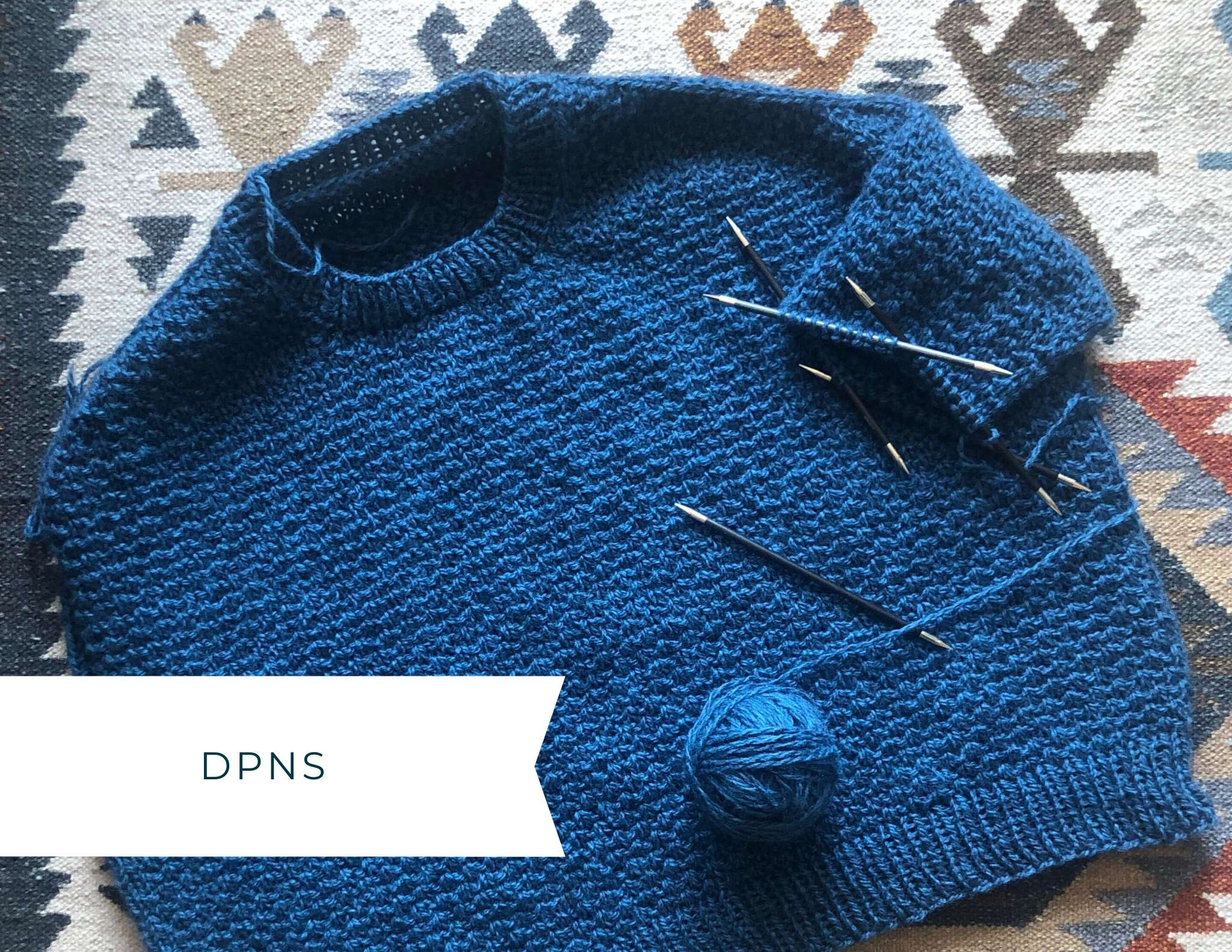 Photo showing a blue glenmore with the sleeve in progress on double pointed needles