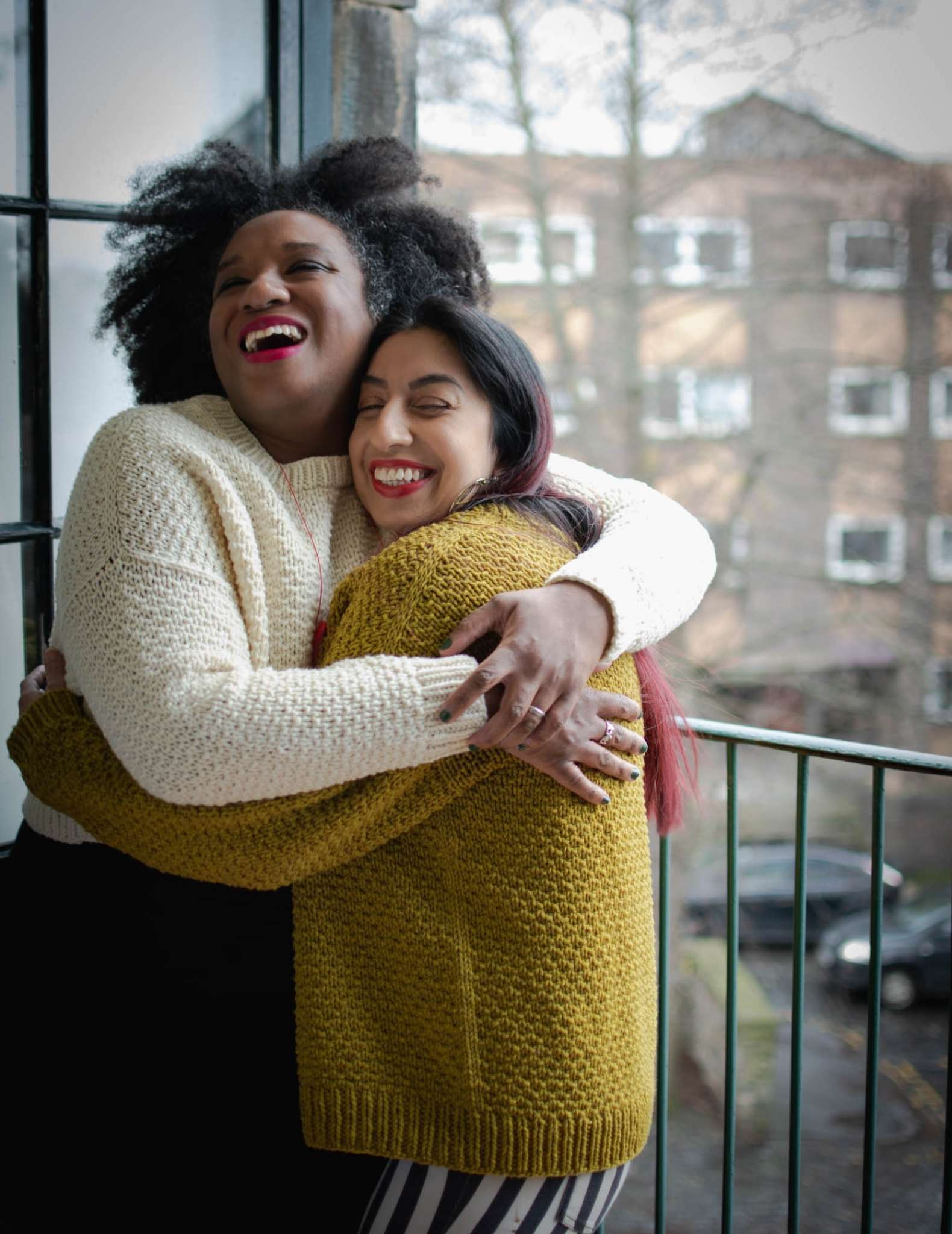 Two models stand indoors in front of a window, looking out onto a street. One wears a cream sweater and the other wears a gold sweater, they have their arms around each other in a tight hug and are grinning.