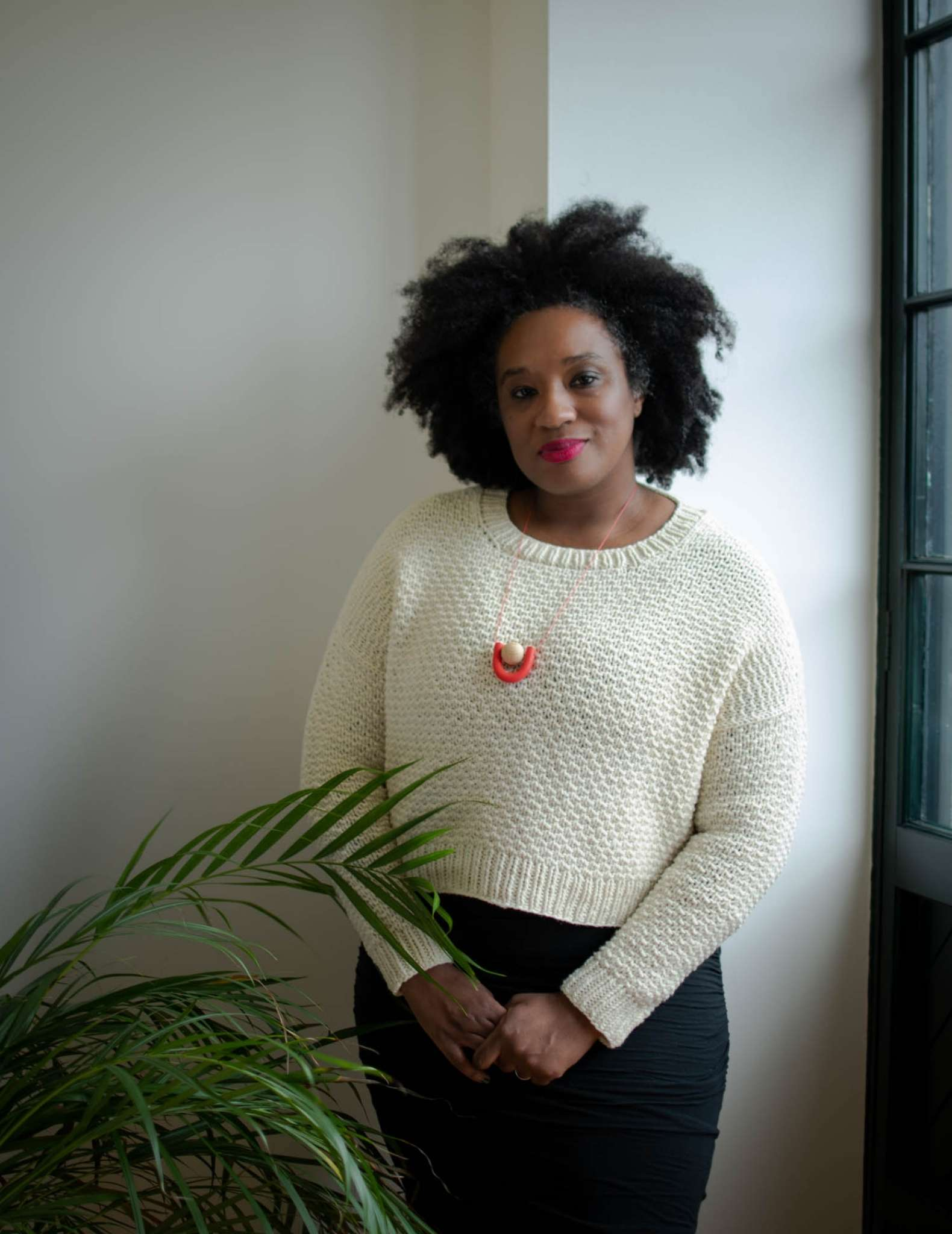 a black woman wearing a cropped white sweater stands beside a houseplant, her hands are clasped together in front of her and she wears an orange necklace