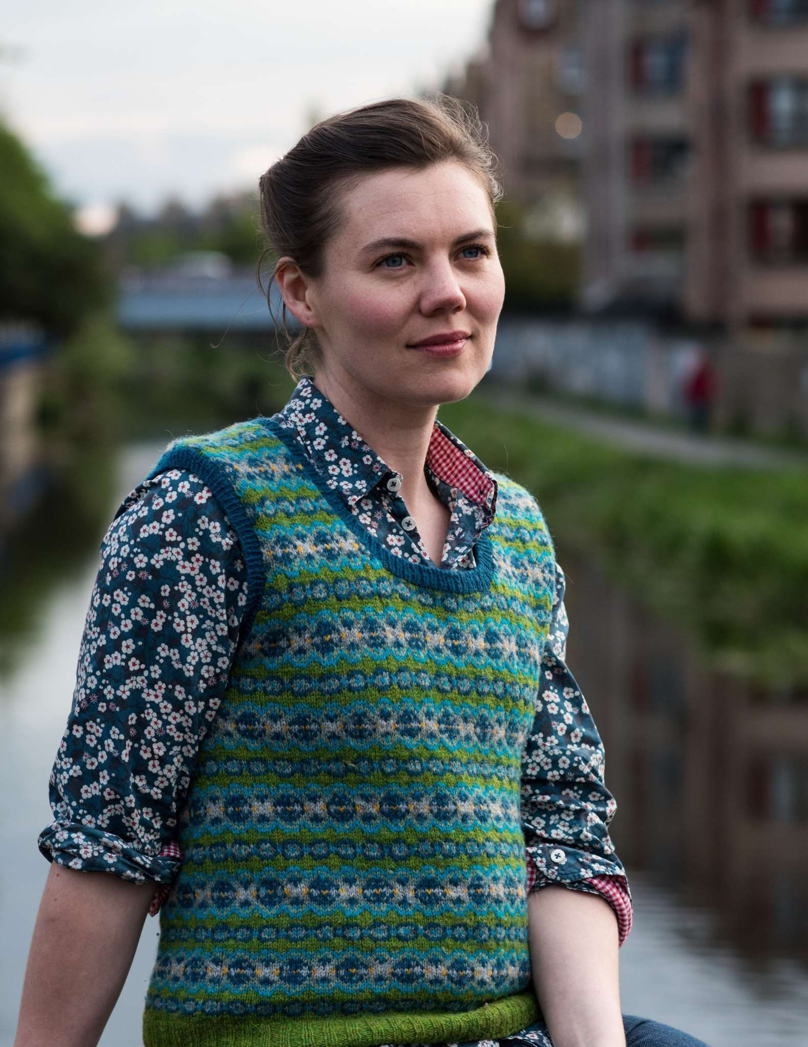 a young white woman wears a colourwork vest in greens and blues over a patterned blue shirt. Her hair is tied back and behind is the water of a canal and buildings to the side.