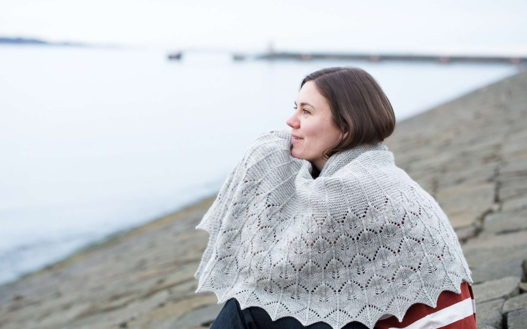 A white woman with brown hair sits huddled on a beach, looking out to sea. She has a large grey shawl wrapped around her and is resting her head in her hands, which are underneath the shawl.