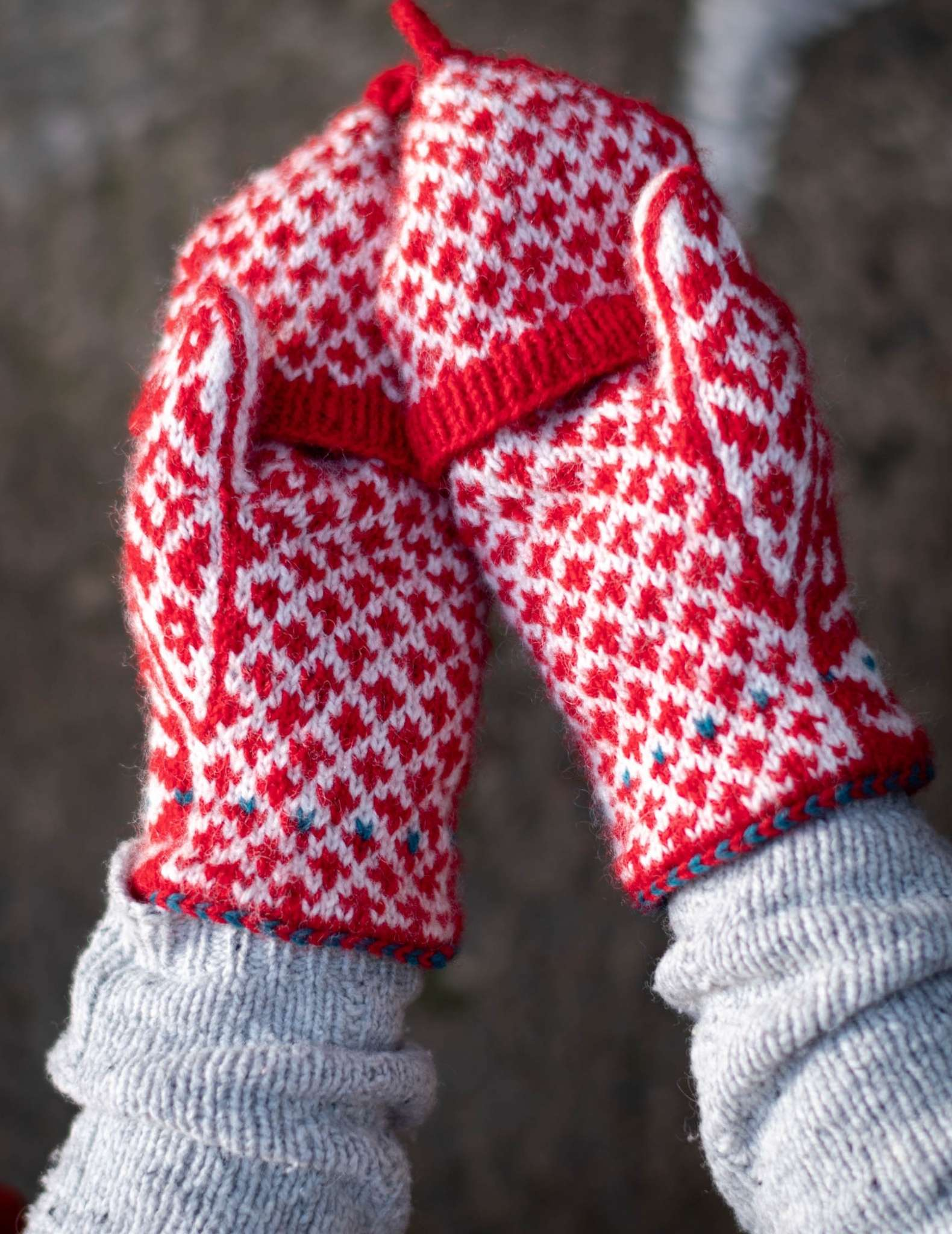 Hands wear a pair of colourwork mittens in red and white, and are held side by side with the palms facing up.