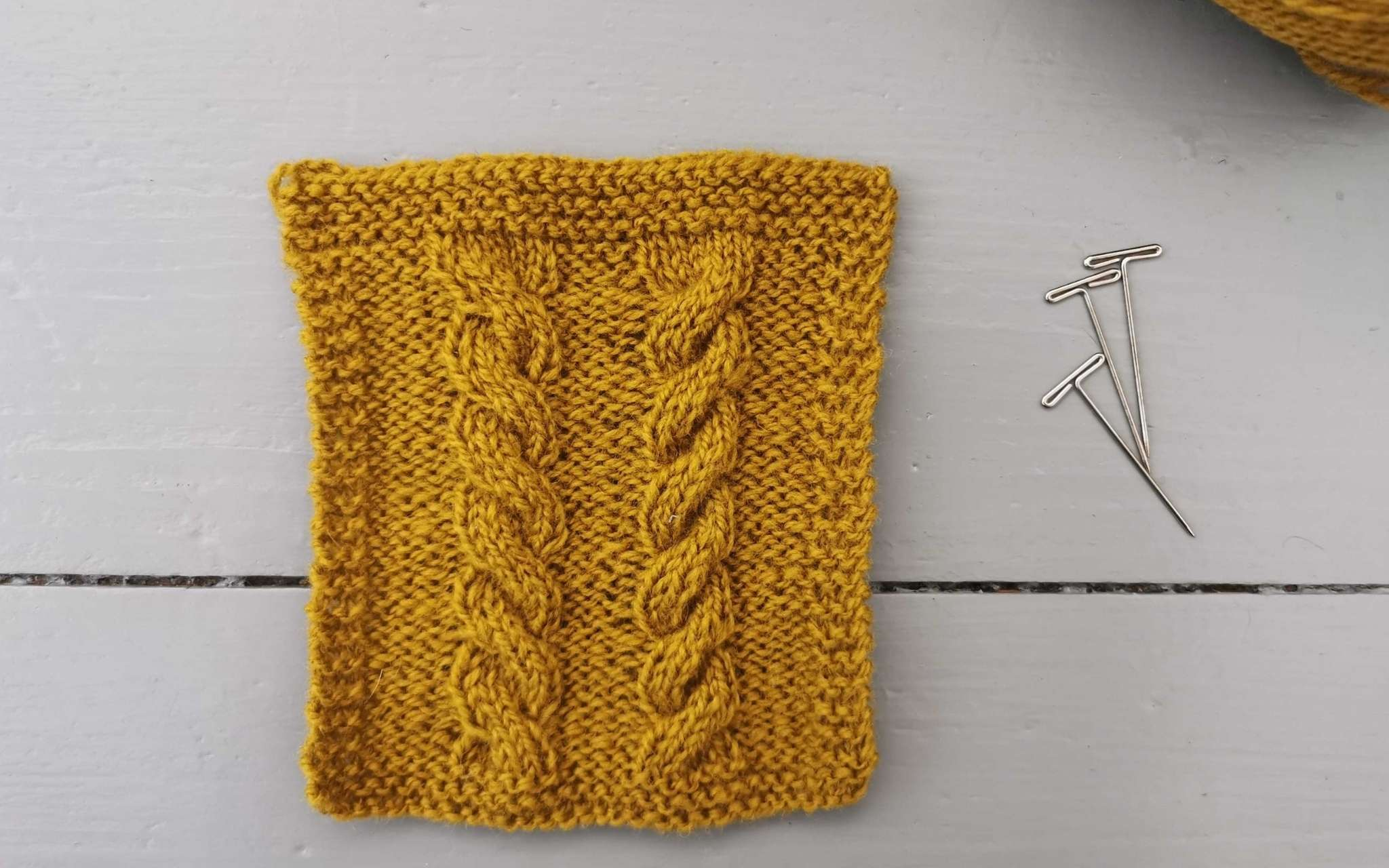 a golden yellow swatch with two cables running up the centre, photographed on a grey wooden background. Three t-pins are at the side and a glimpse of the ball of yarn used in the corner