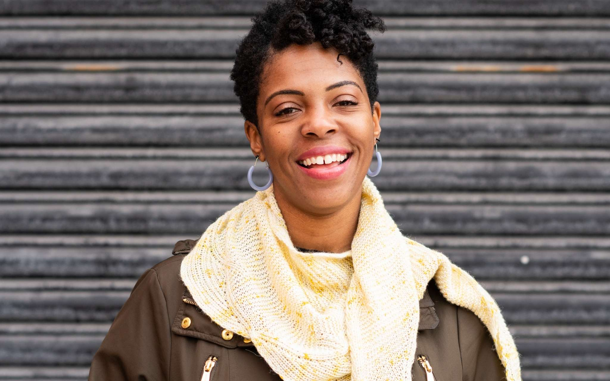 A young black woman with short hair and hoop earings stands in front of an iron door. She is wearing a pale lemon shawl with a brown jacket and is smiling.