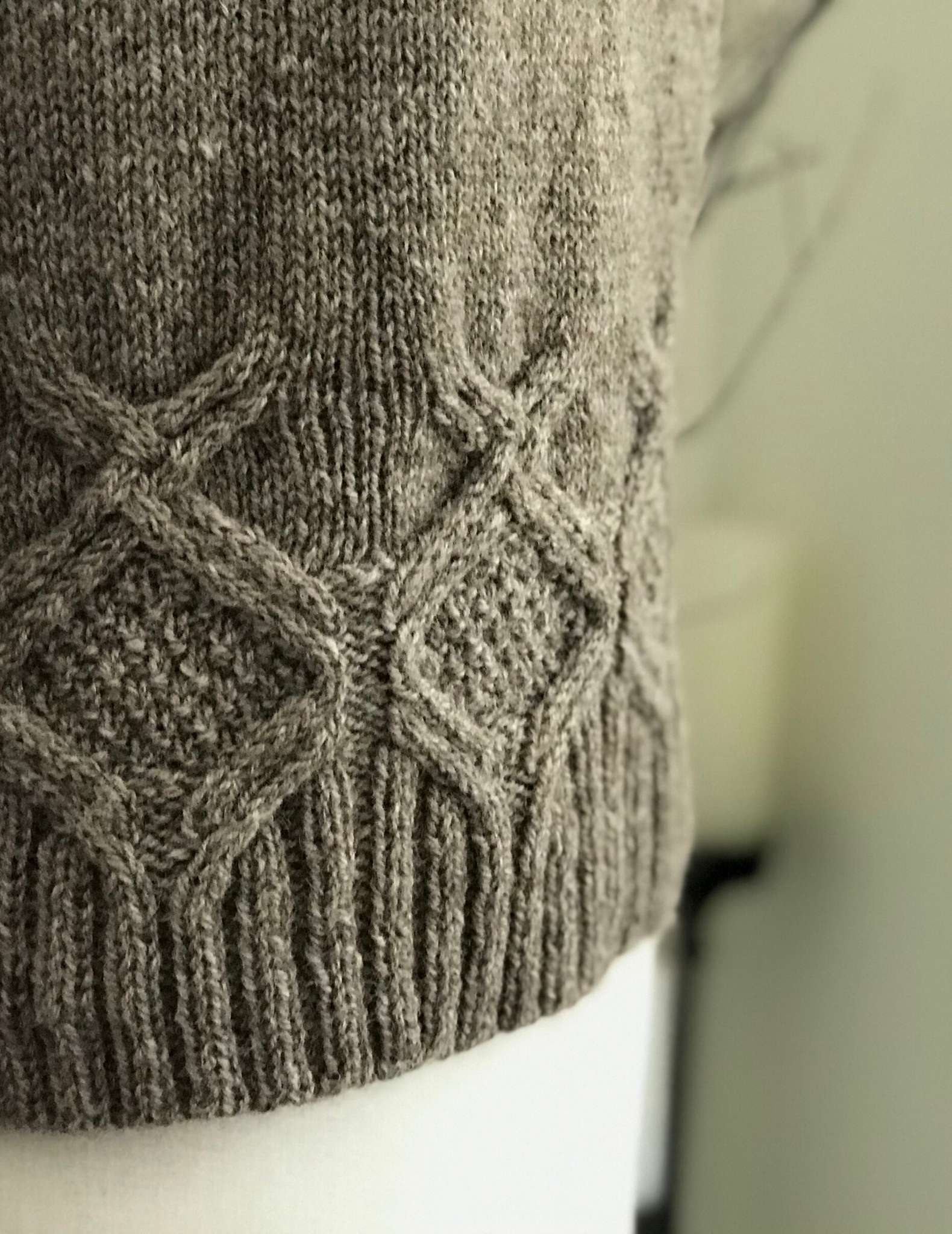 close up image of cables around the hem of a sweater, displayed on a mannequin