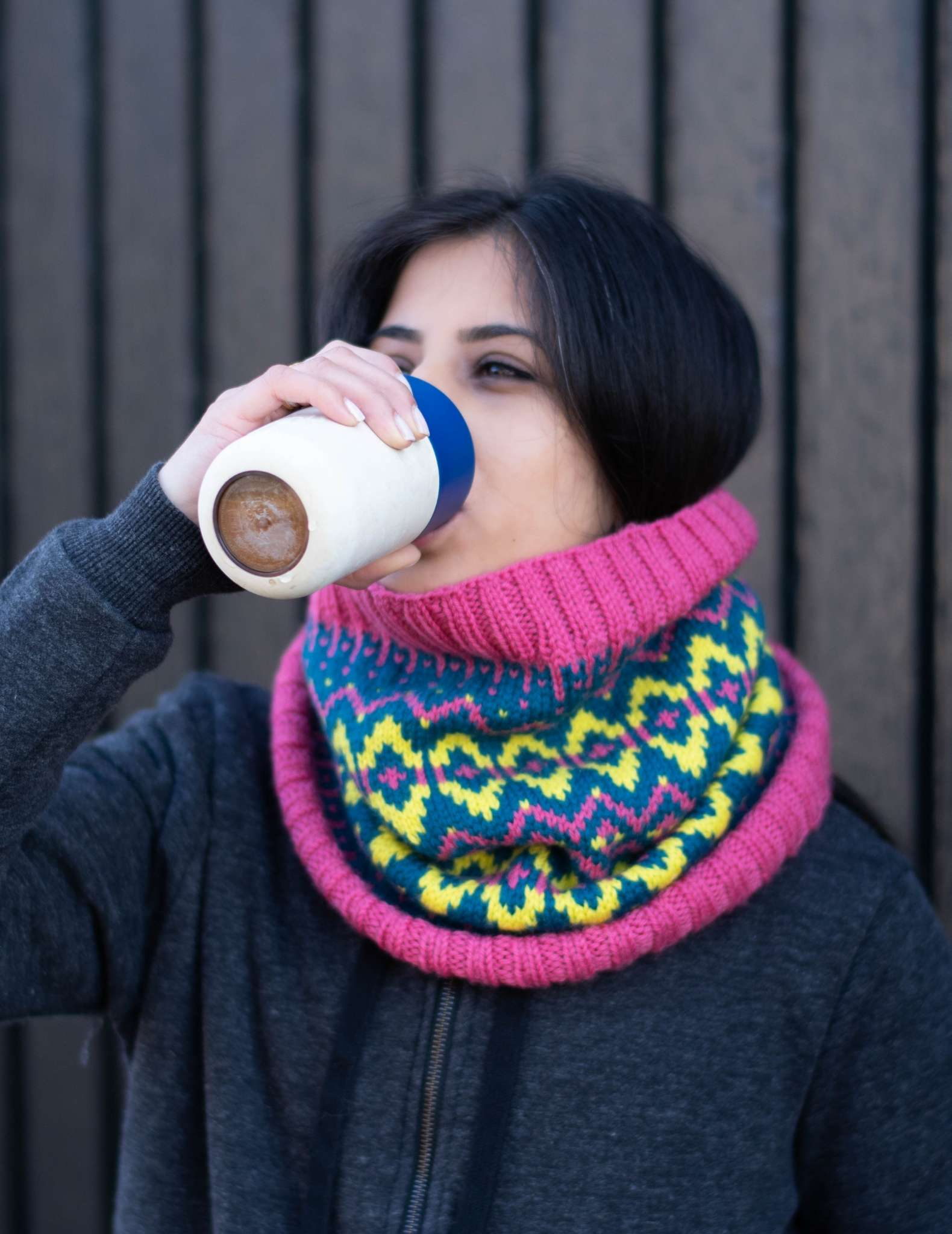 a woman with dark hair wears a pink, green and teal colourwork cowl, she is drinking from a coffee cup