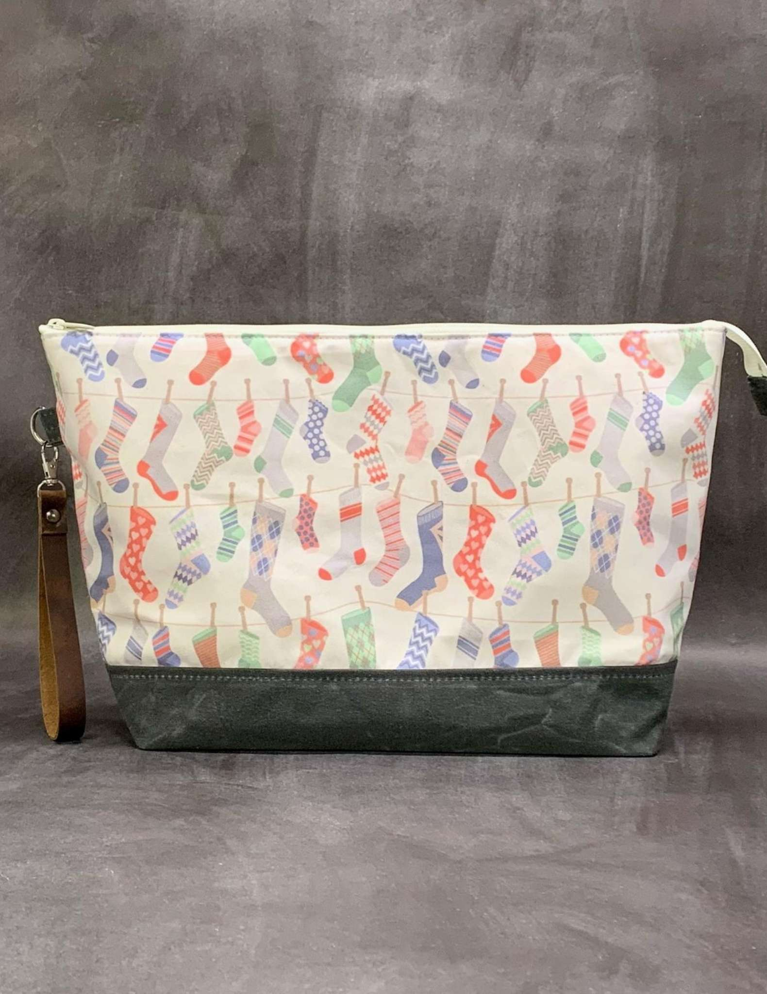 A project bag with zip made in a fabric print of hanging socks