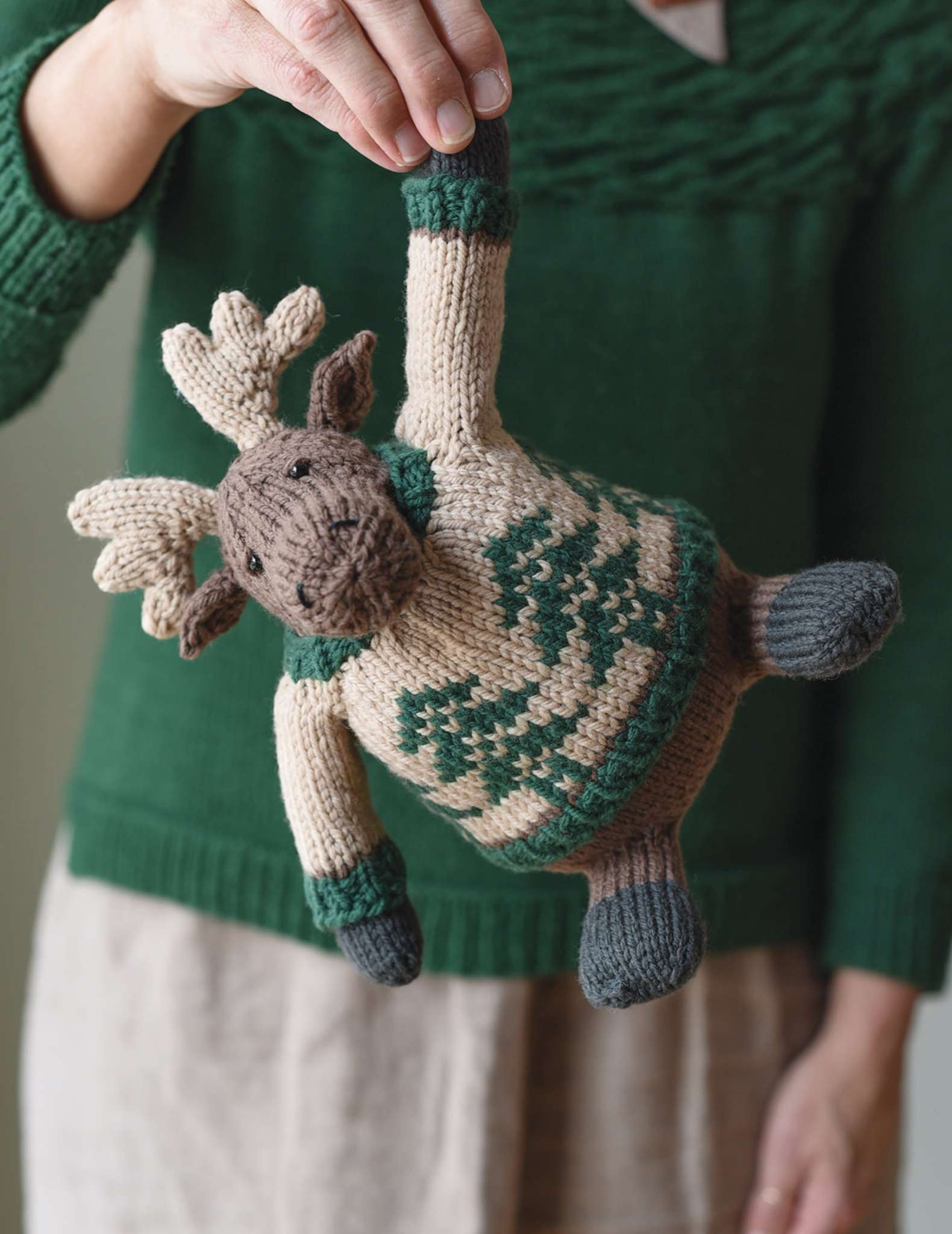 A knitted toy moose is hanging down in front of a model, being held by one arm. The moose wears a colourwork sweater with a tree motif. The model has white hands and is wearing a green sweater.