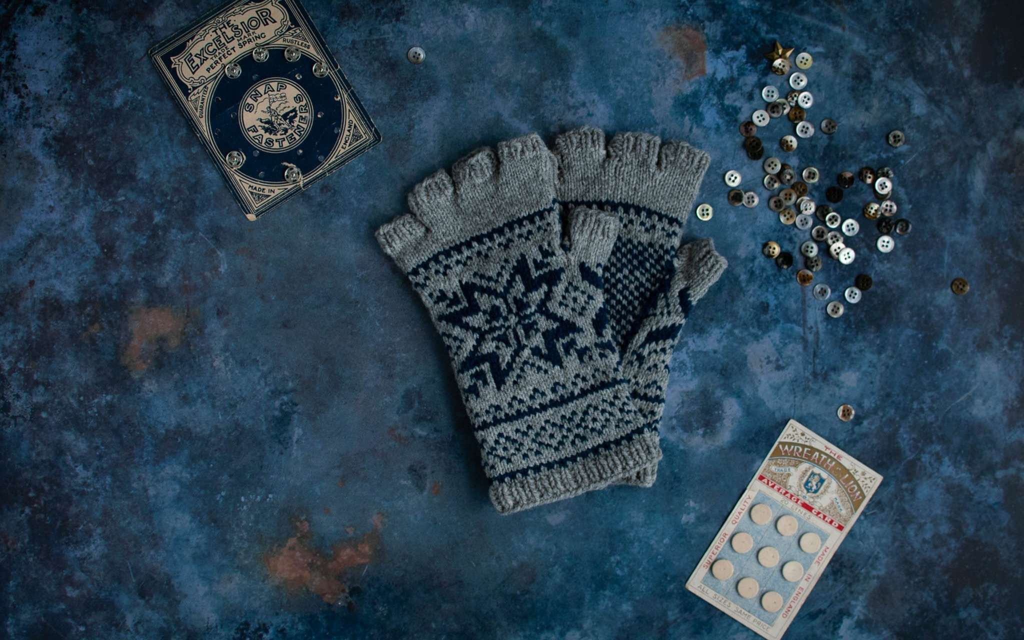 A pair navy and grey colourwork fingerless gloves lay flat on a moody blue background. Next to them are piles of blue and grey vintage buttons.