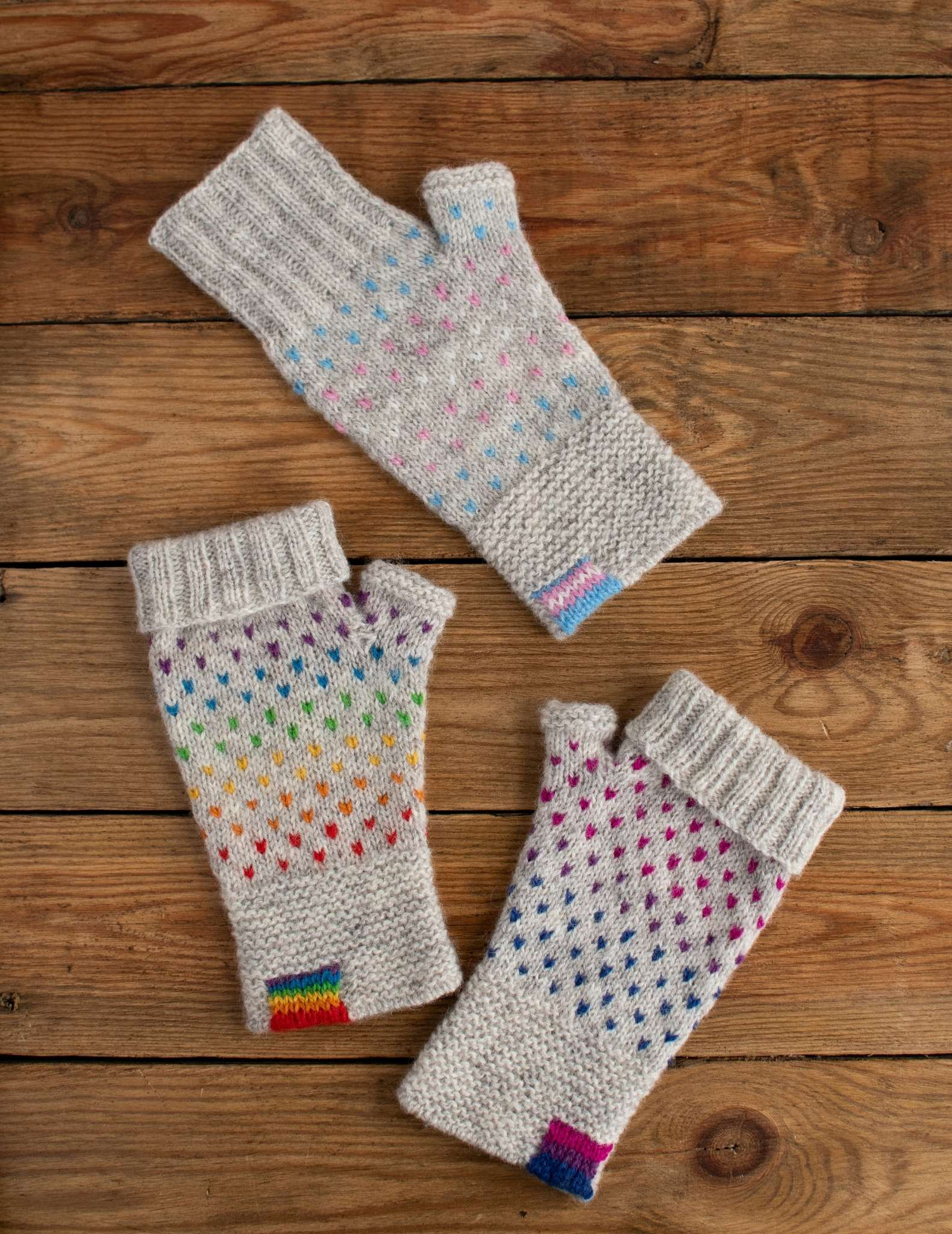 three individual fingerless mitts lay flat on a wooden surface. Each features a dot pattern on a grey background and a flag on the cuff in pride, bi, and transgender colours