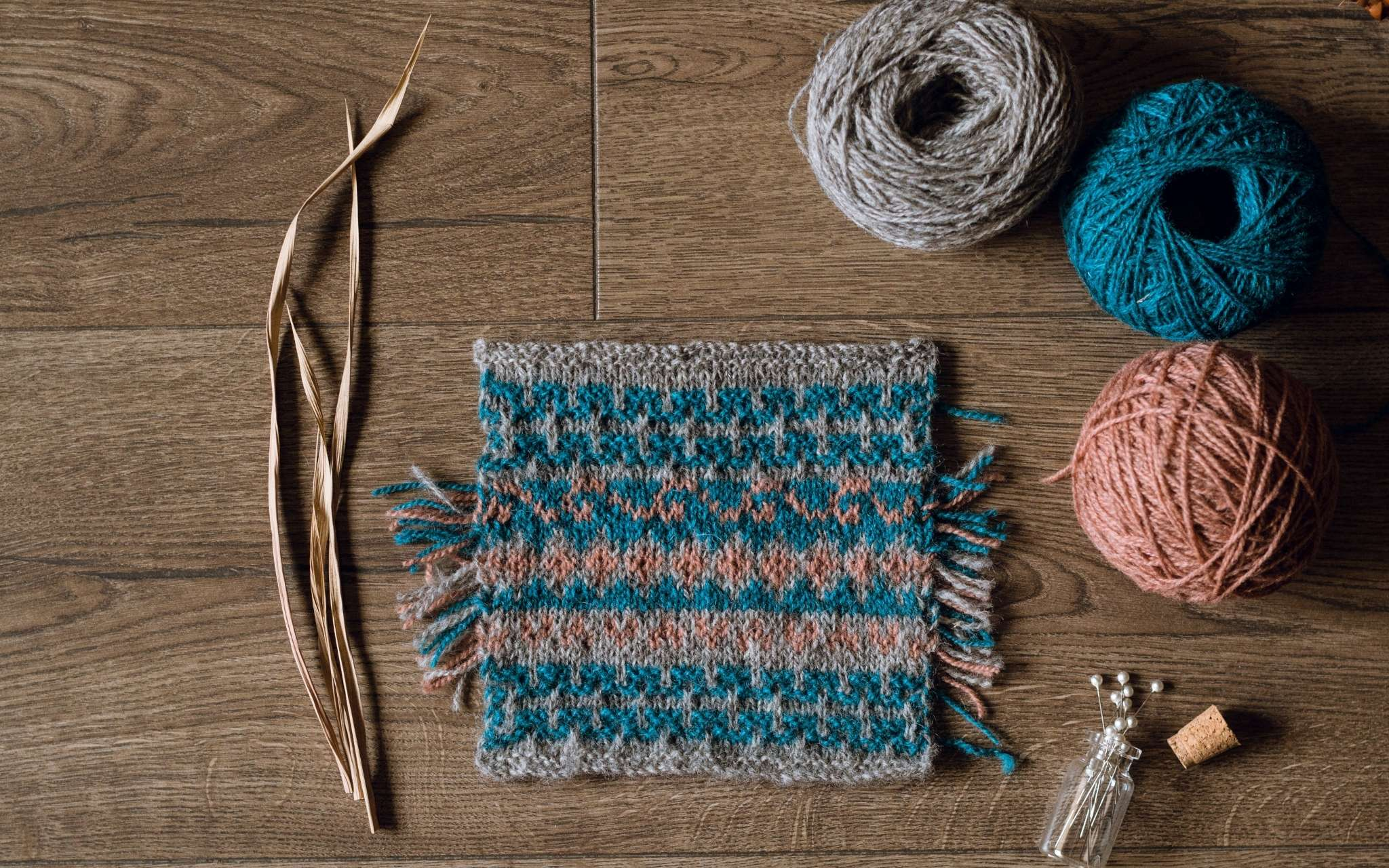 A swatch of colourwork knitting in dark blue, coral and grey laid flat on a wooden surface. There are some dried stems, scissors and a bottle of pints to the side.