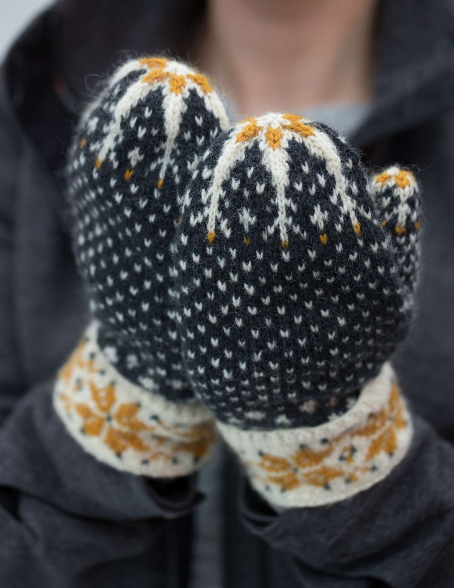 A close up of hands held close together wearing colourwork mittens in dark blue, gold and white. The cuffs and mitten tops features a snowflake motif.