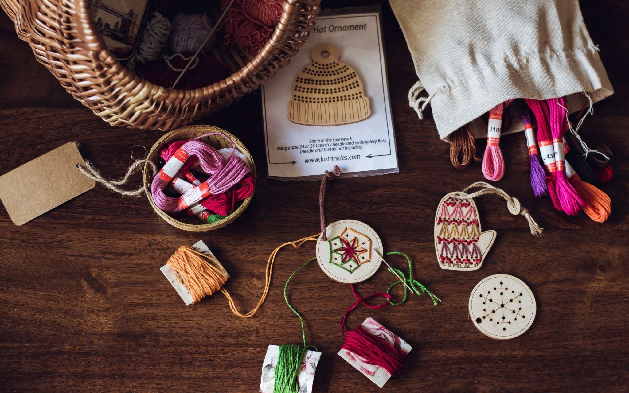 A selection of wooden hanging ornaments lie on a flat surface next to a wicker basket, and a pile of brightly coloured threads.